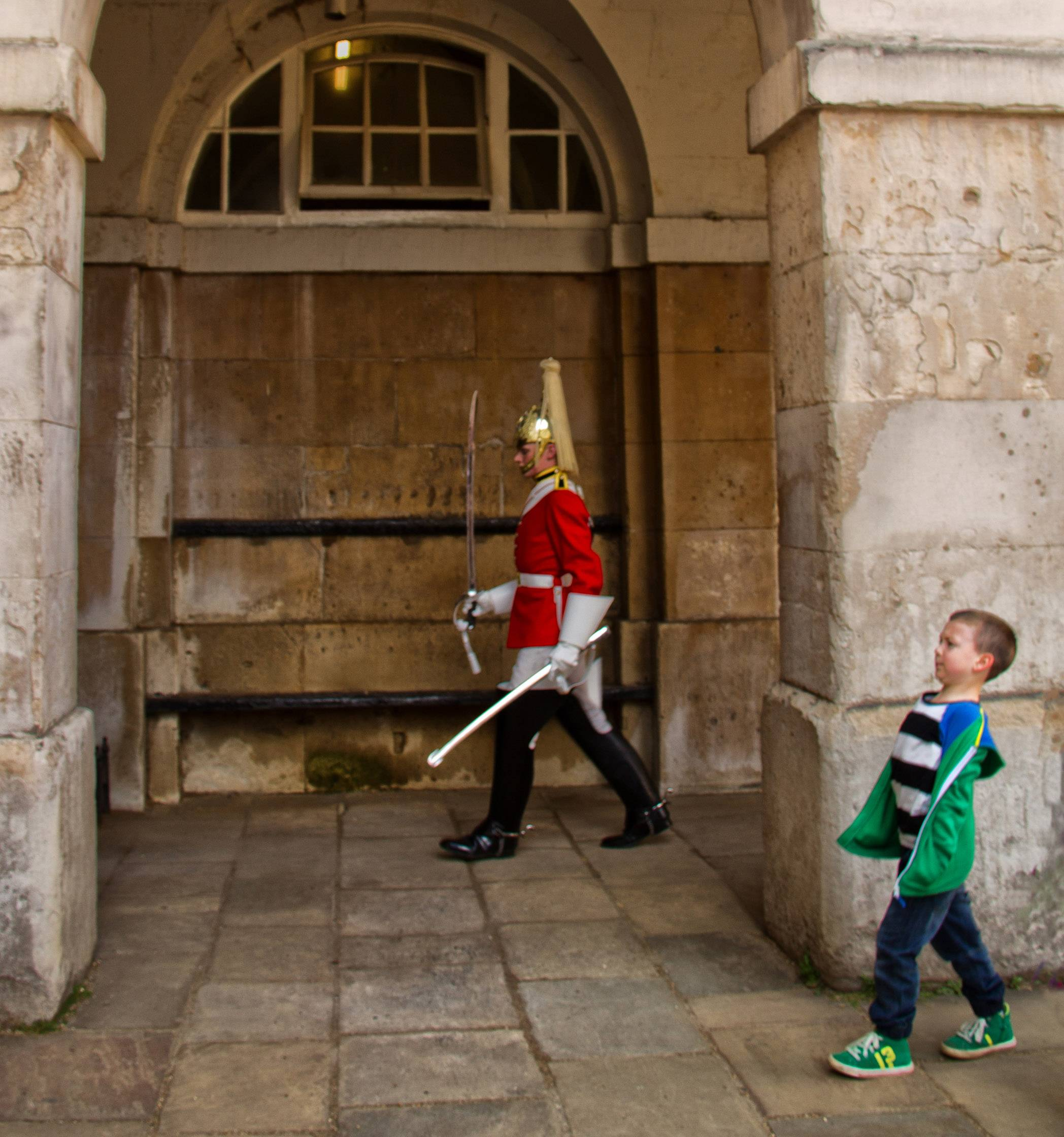 A young boy enjoys trying to march like the Queen's Guard at Buckingham Palace in the area adjacent to the palace in London.