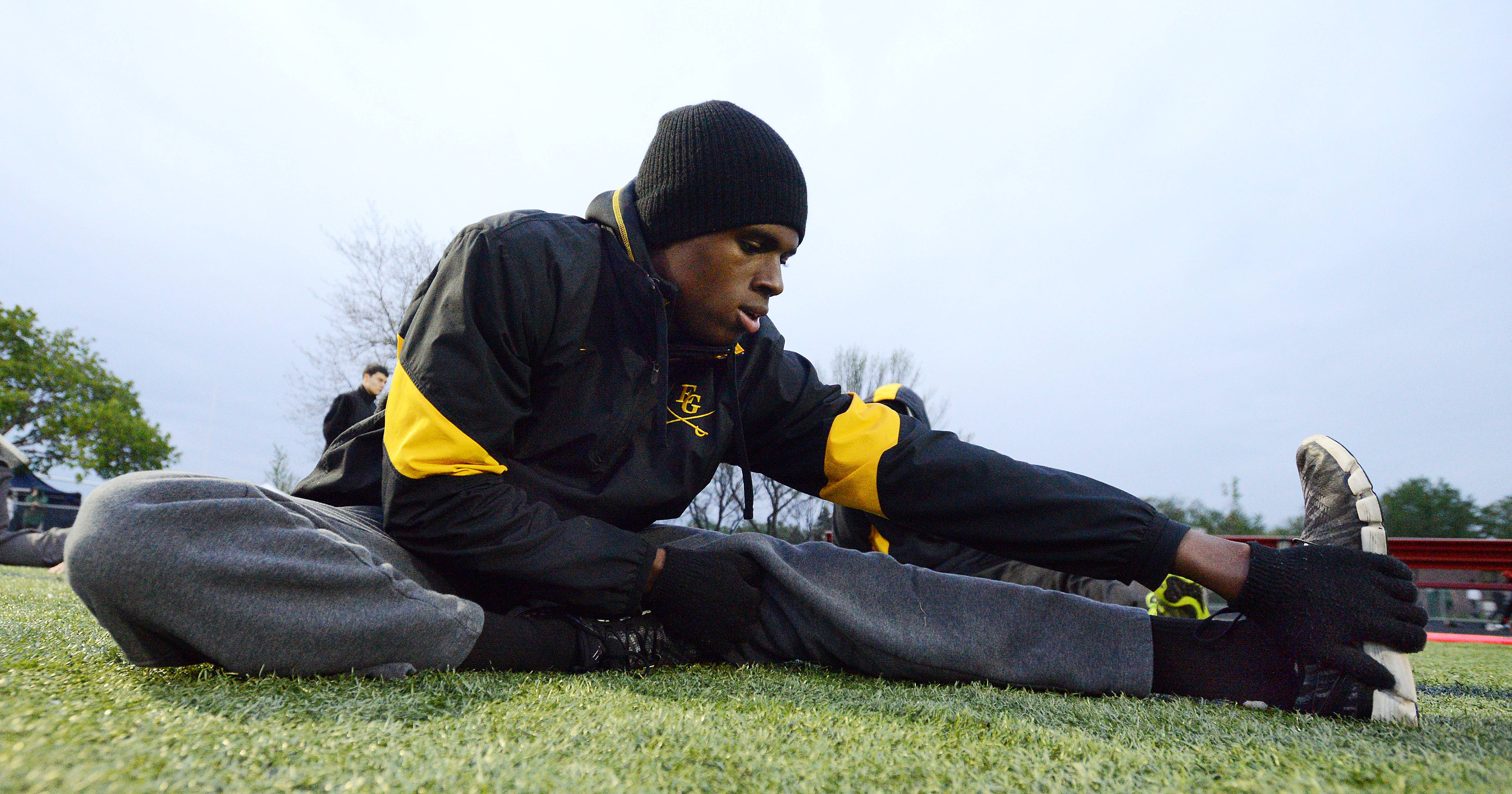 Elk Grove's Paul Ifianyi warms up before his races during the Mid-Suburban League meet Friday at Palatine.