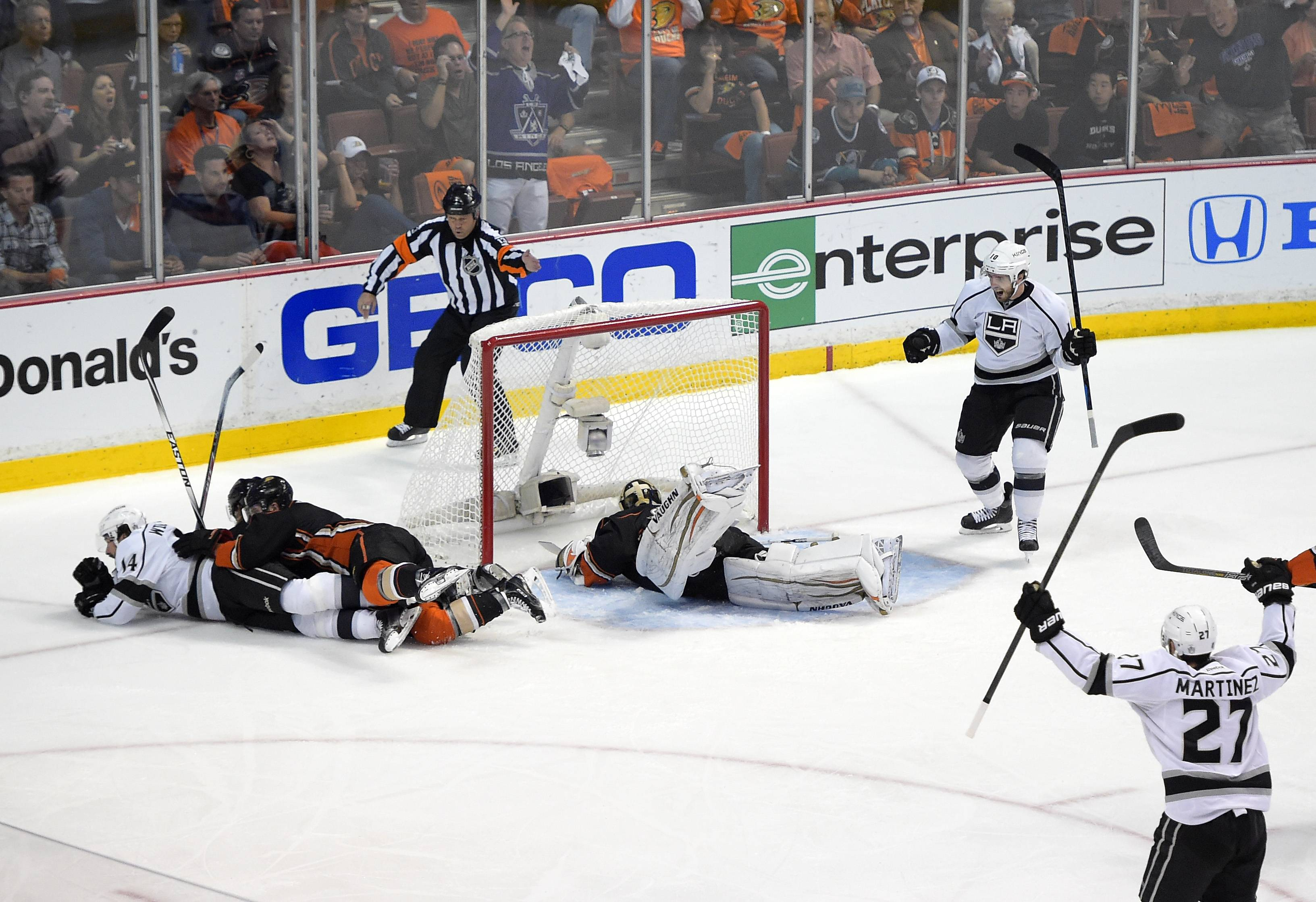 Anaheim Ducks defenseman Cam Fowler, third from left, and defenseman Sami Vatanen, of Finland, second from left, lie on Los Angeles Kings right wing Justin Williams, left, who scored on Anaheim Ducks goalie John Gibson, center, as Kings center Mike Richards, upper right, and defenseman Alec Martinez, lower right, celebrate during the first period in Game 7 of an NHL hockey second-round Stanley Cup playoff series, Friday, May 16, 2014, in Anaheim, Calif.