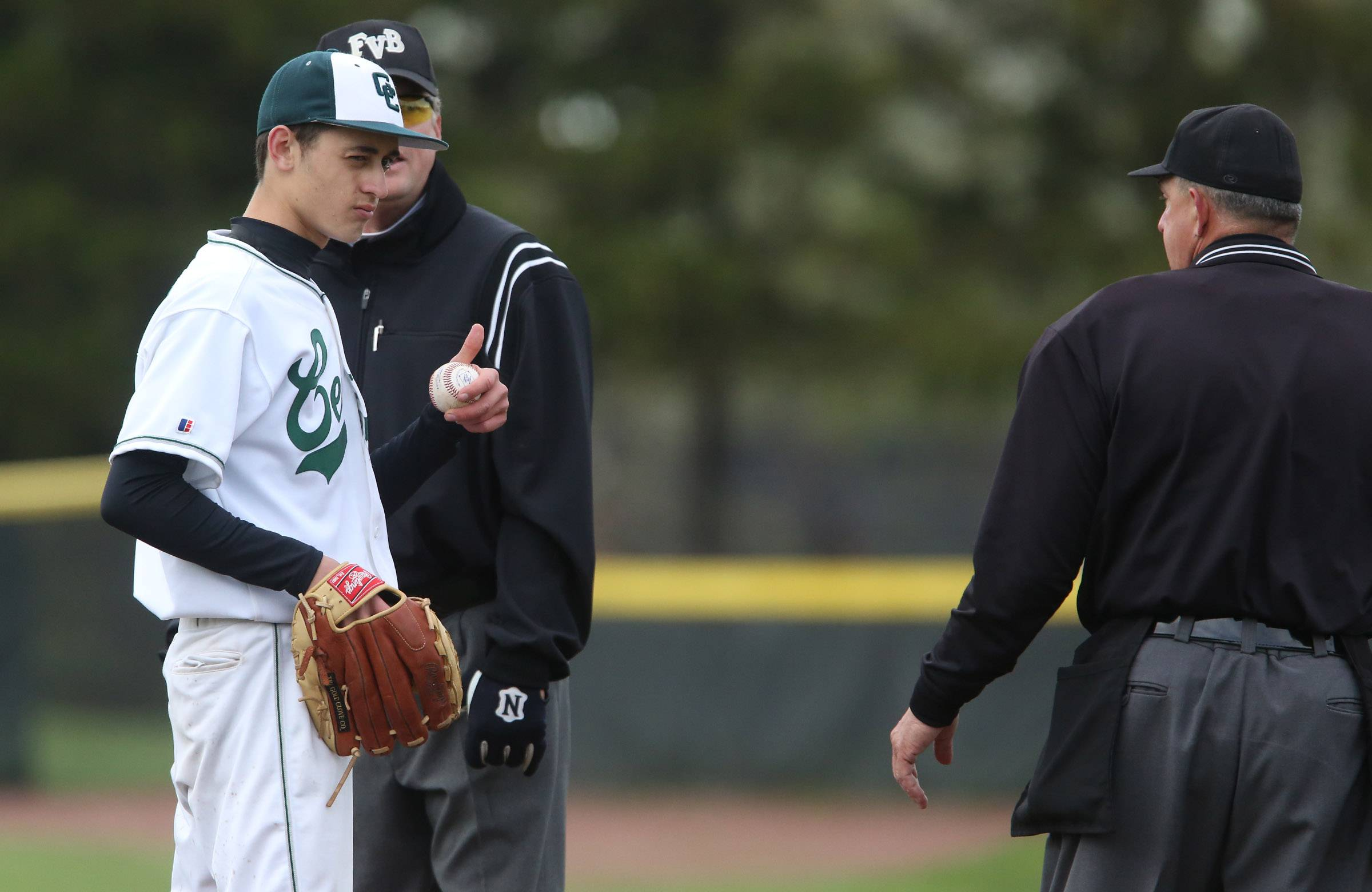 Grayslake Central pitcher Justin Guryn shows the umpire he has a bandage on his finger after the umpire checked his throwing fingers for an object, against Grayslake North on Friday.