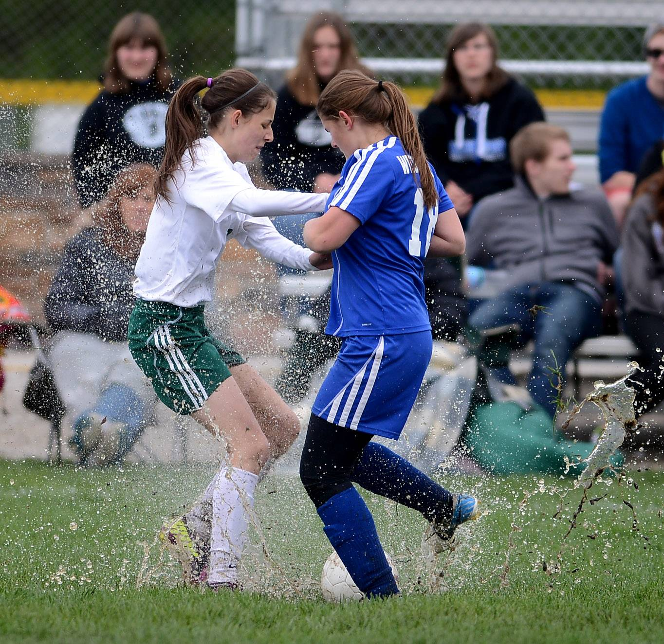 St. Edward's Chelsea Gnan (6) and Westminster Christian's Allie Tanzillo find the field's biggest puddle as they battle for the ball during Friday's regional final in Elgin.
