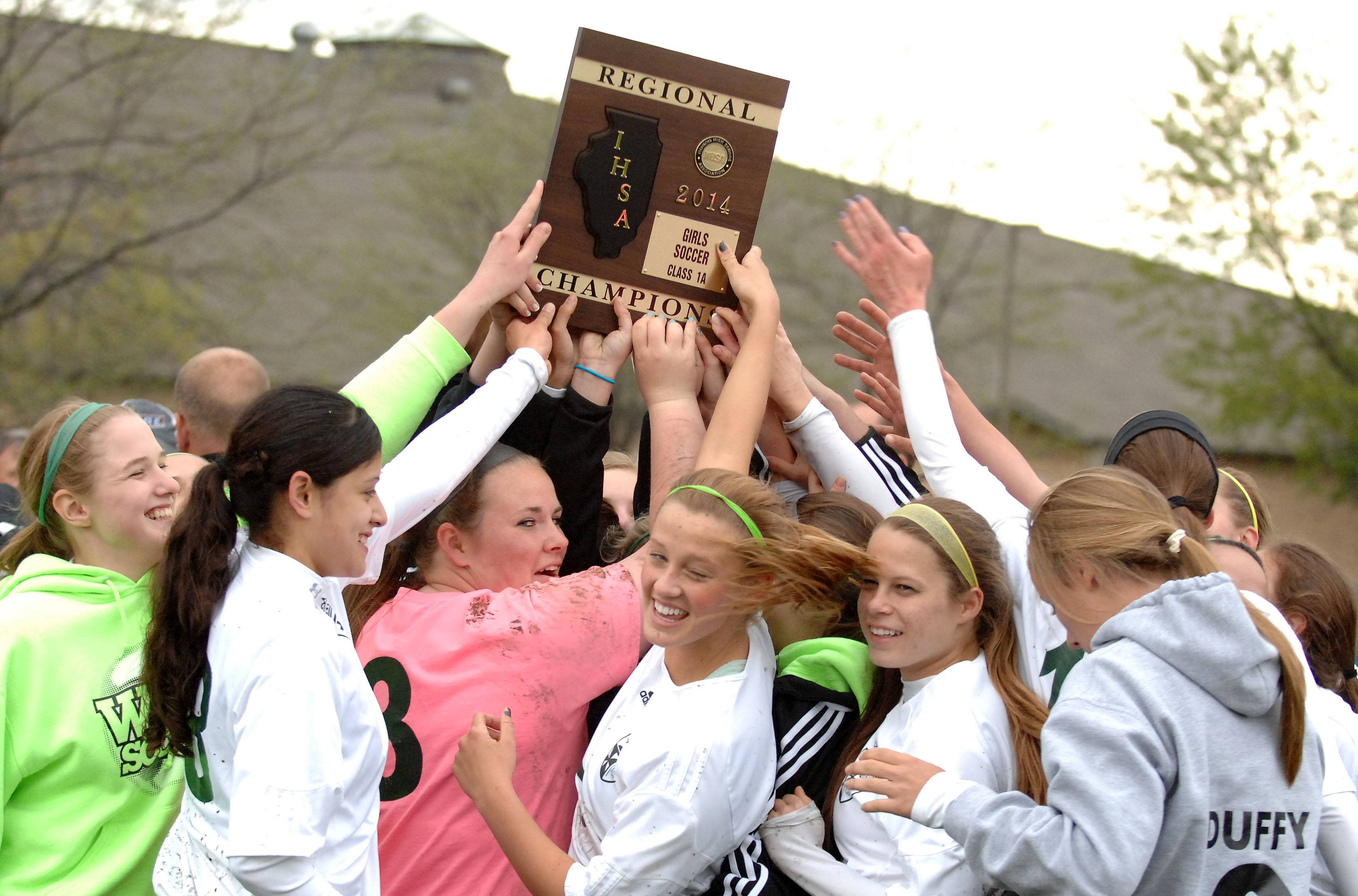 St. Edward players hoist the regional championship plaque following Friday's regional final in Elgin.