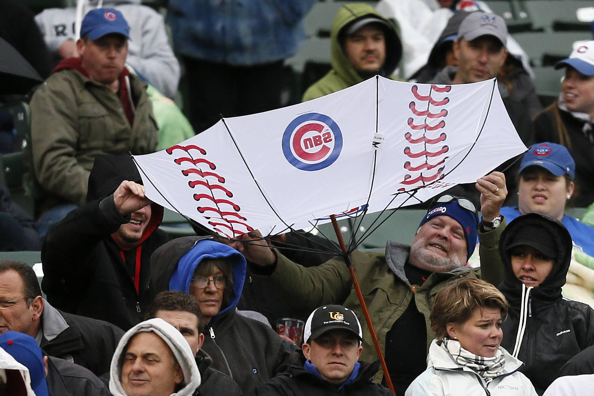 A fan has his umbrella flipped inside out by the wind Friday in the rain and cold at Wrigley Field.