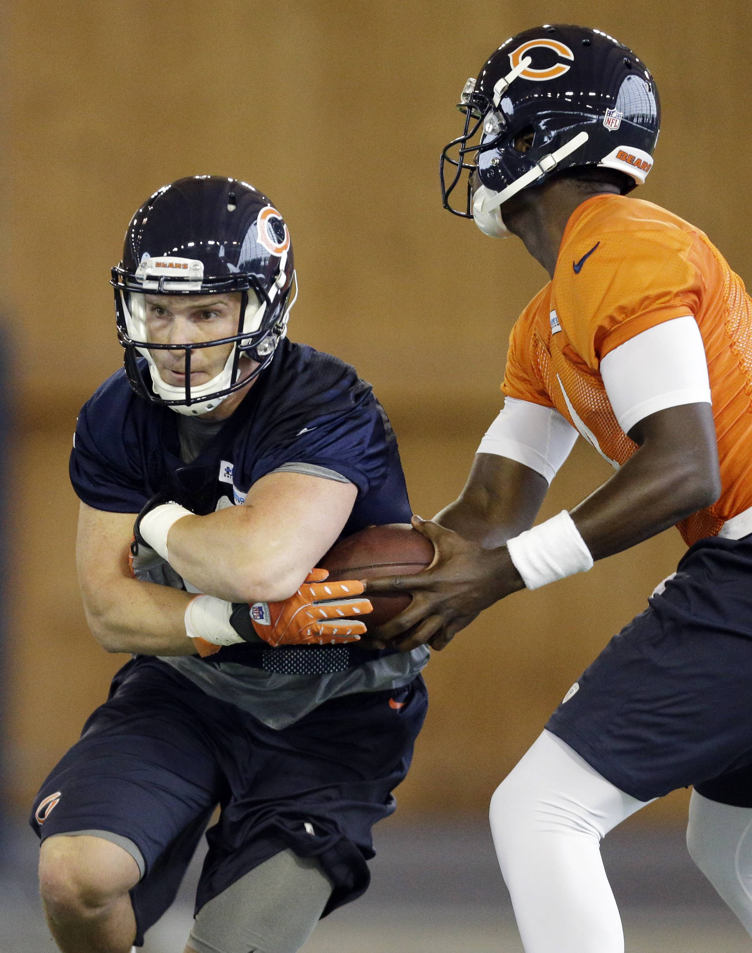 Chicago Bears quarterback Jerrod Johnson, right, fakes the handoff to running back Jordan Lynch, left, takes the handoff during the team's NFL football rookie camp Friday, May 16, 2014, in Lake Forest, Ill.