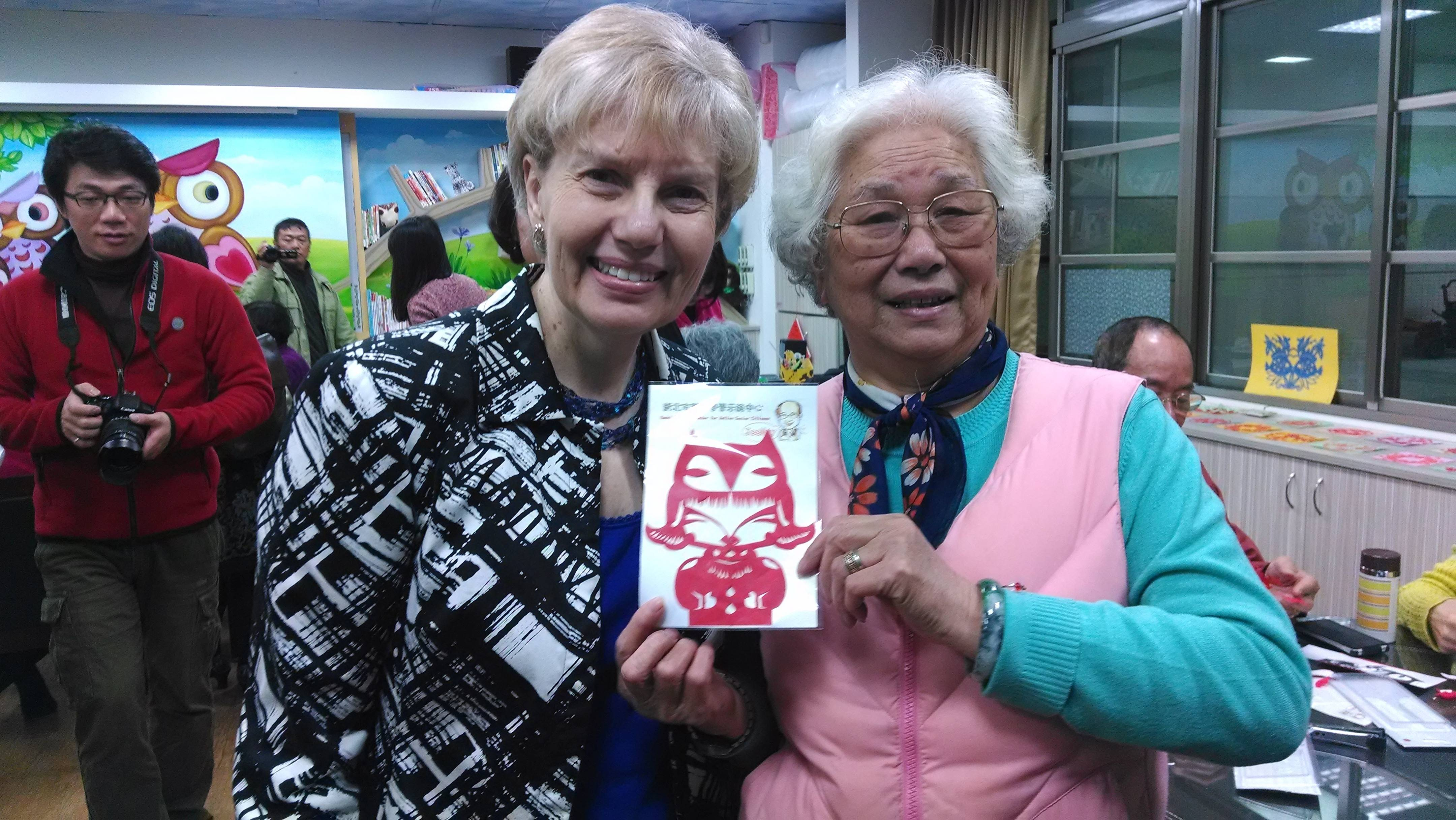 Carol Reagan visits with a participant of the Ji Mei Senior Citizens Learning Center, in New Taipei City.