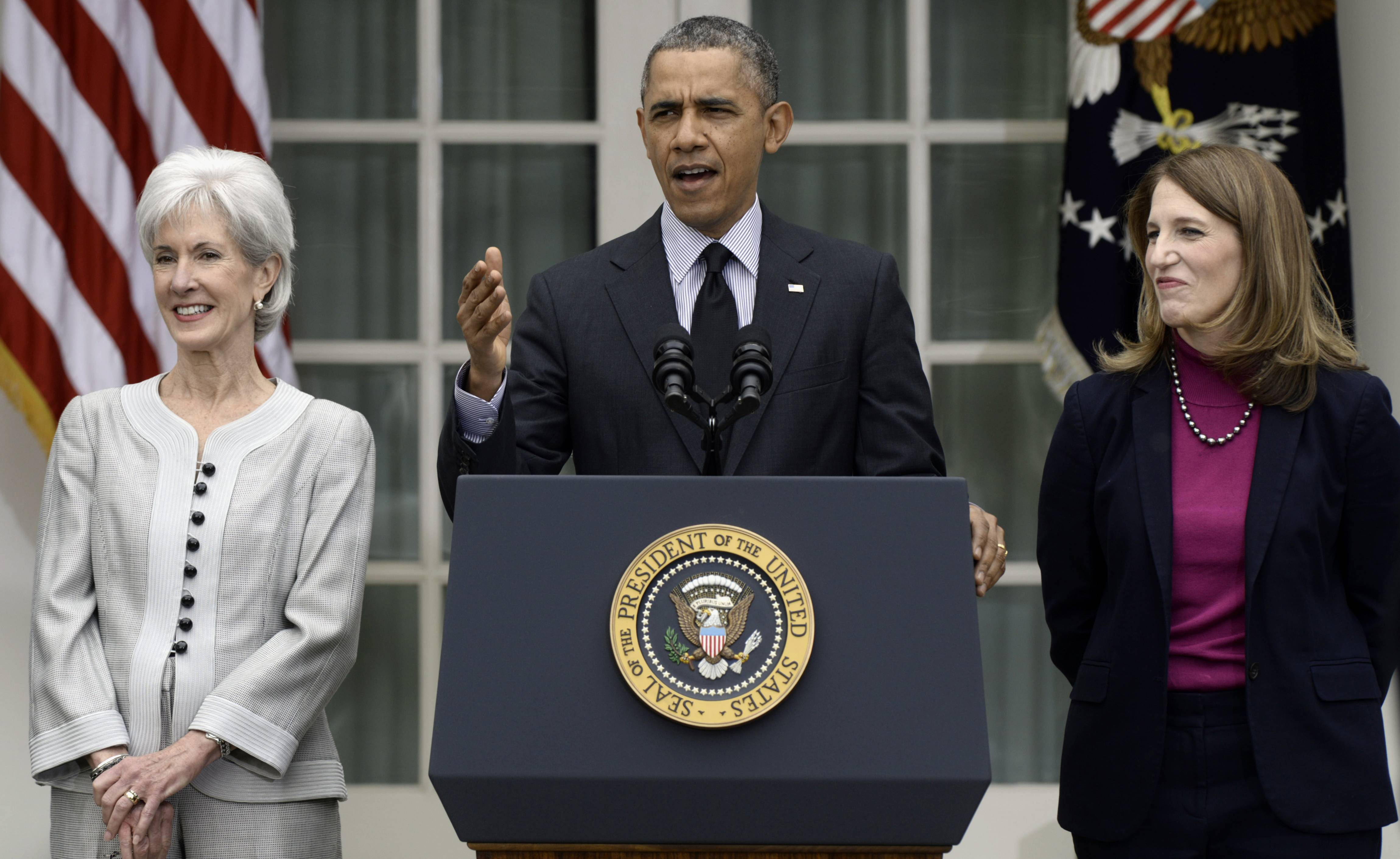 This April 11, 2014 file photo shows President Barack Obama, flanked by outgoing Health and Human Services Secretary Kathleen Sebelius, left, and his nominee to replace her, current Budget Director Sylvia Mathews Burwell, speaking in the Rose Garden of the White House in Washington.