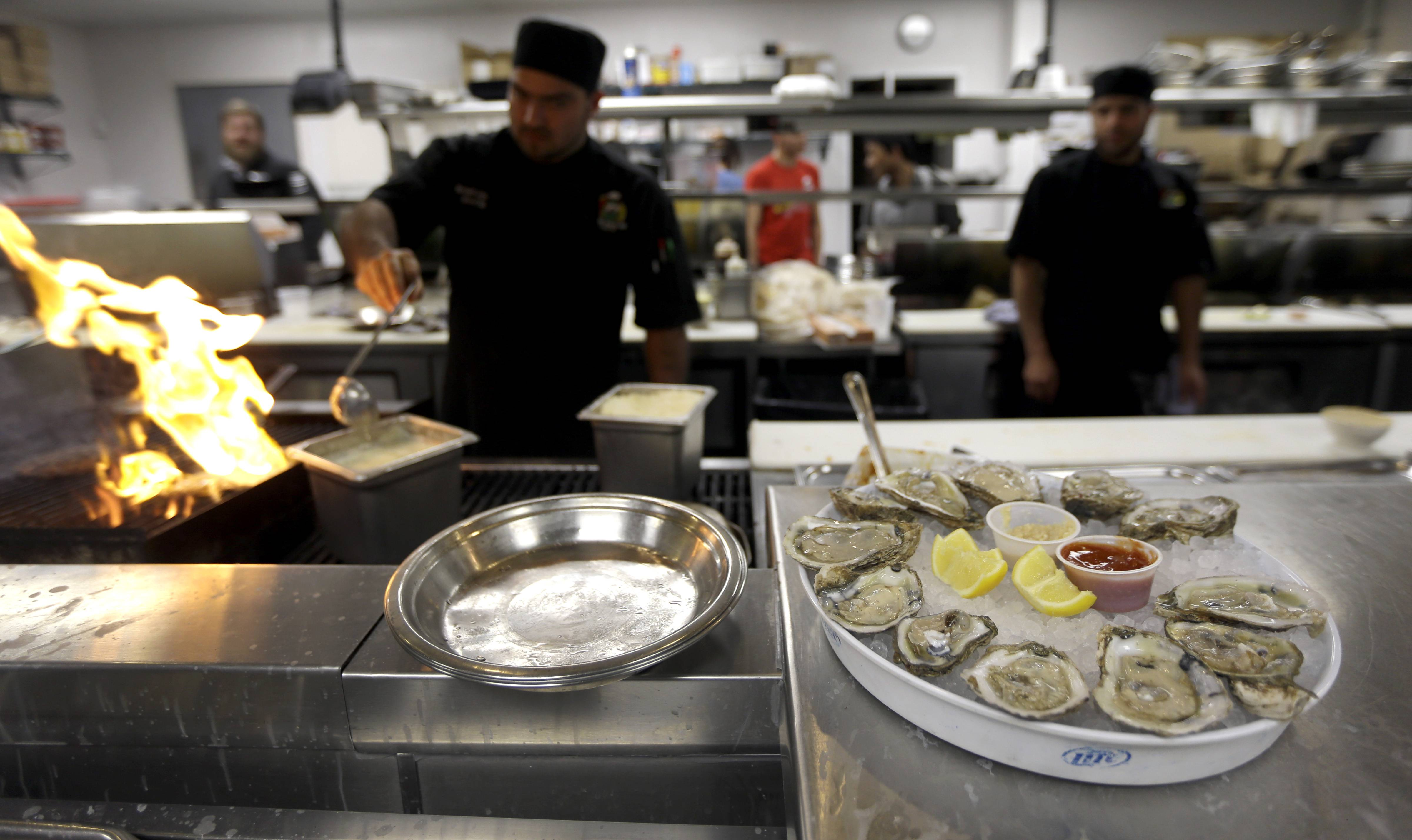 Sous chef Arturo Morales, left, prepares a dish at the grill as a plate of oysters sit ready to be served at Broadway Oyster Bar in St. Louis.