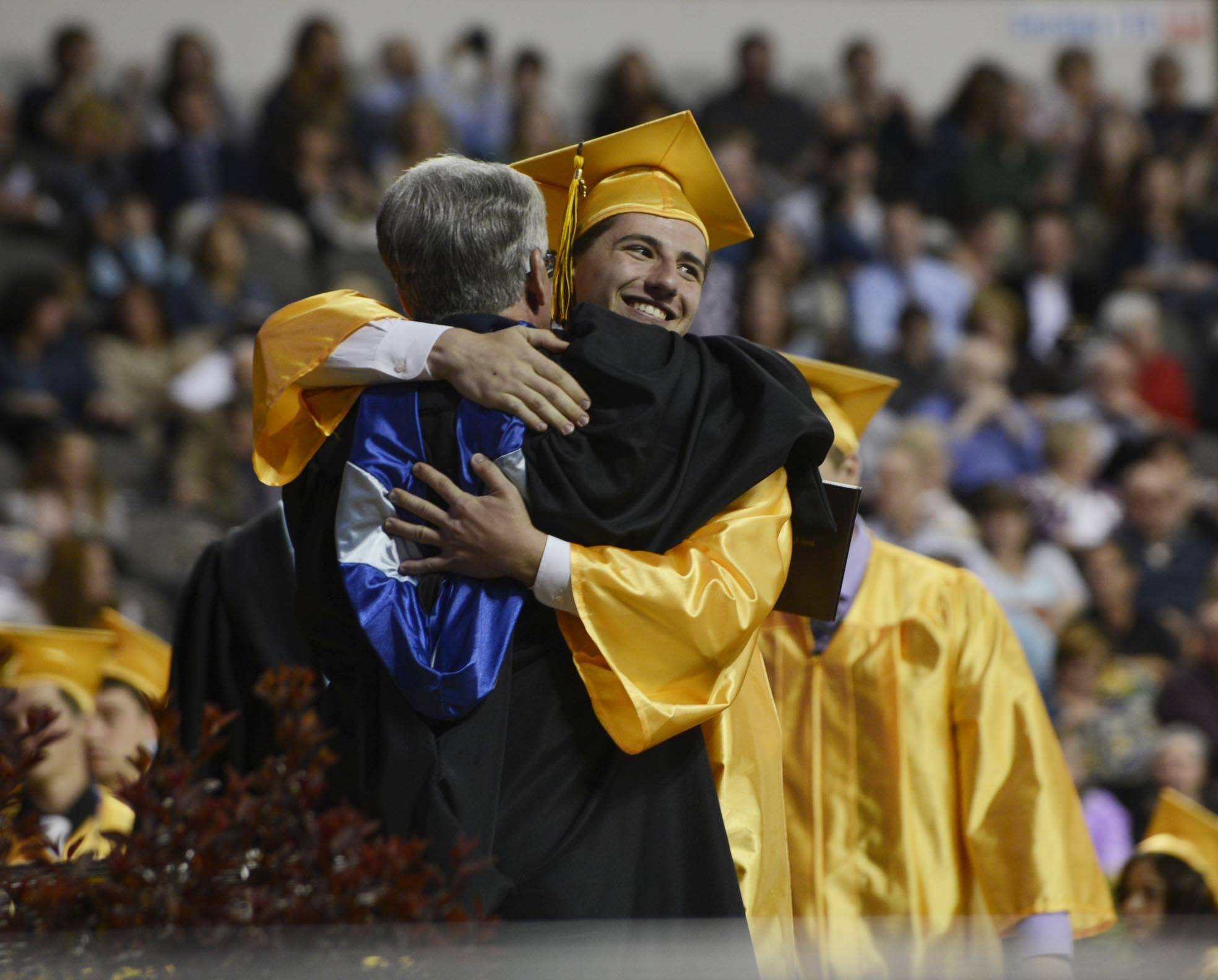 John Starks/jstarks@dailyherald Graduate Salvatore James Leonard gets a hug onstage as he receives his diploma Saturday at the Harry D. Jacobs High School 2014 Commencement at the Sears Center in Hoffman Estates.