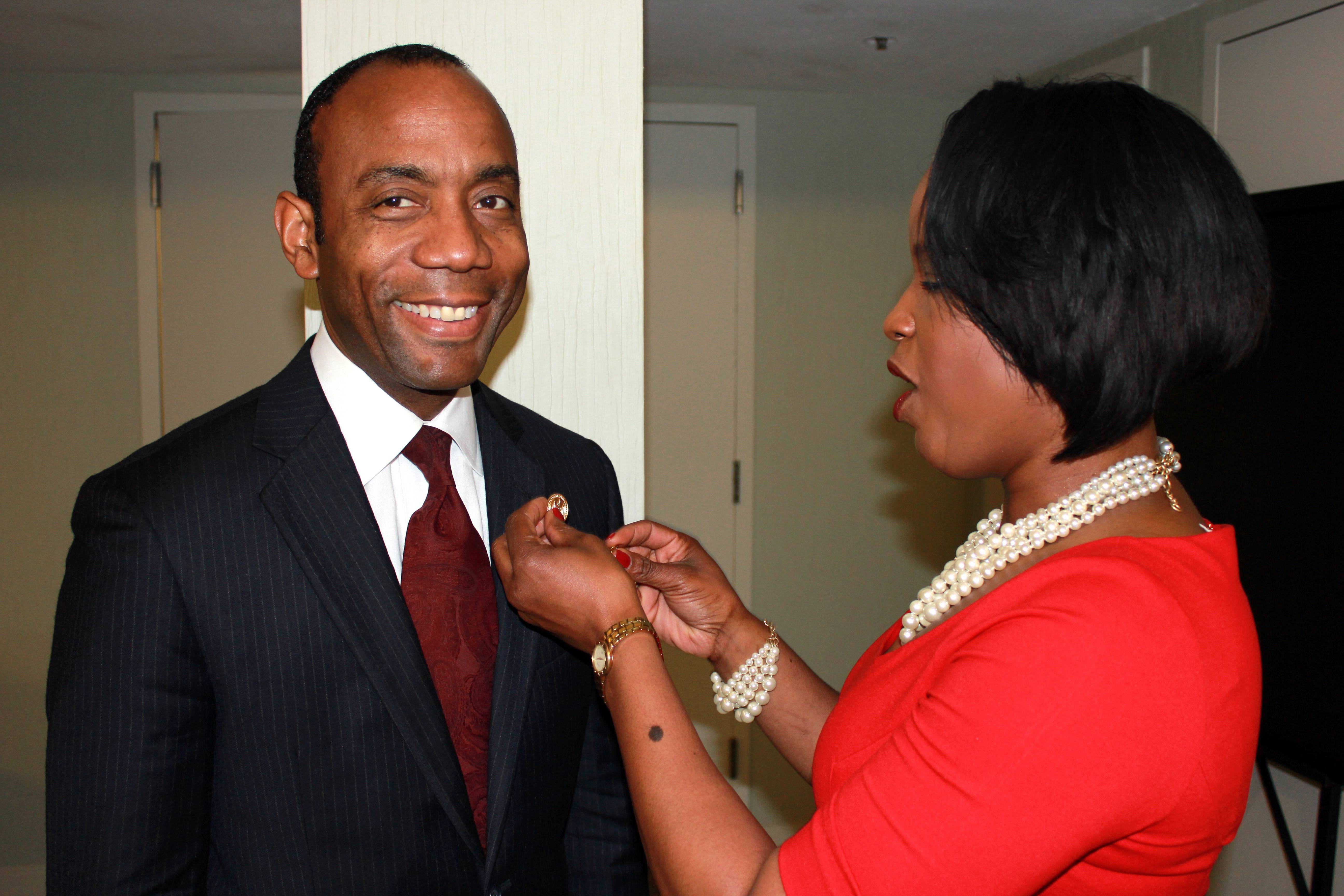 Roslyn Brock, right, chairman of the national board of directors for the NAACP, puts an NAACP pin on new national president and CEO, Cornell William Brooks on Saturday.
