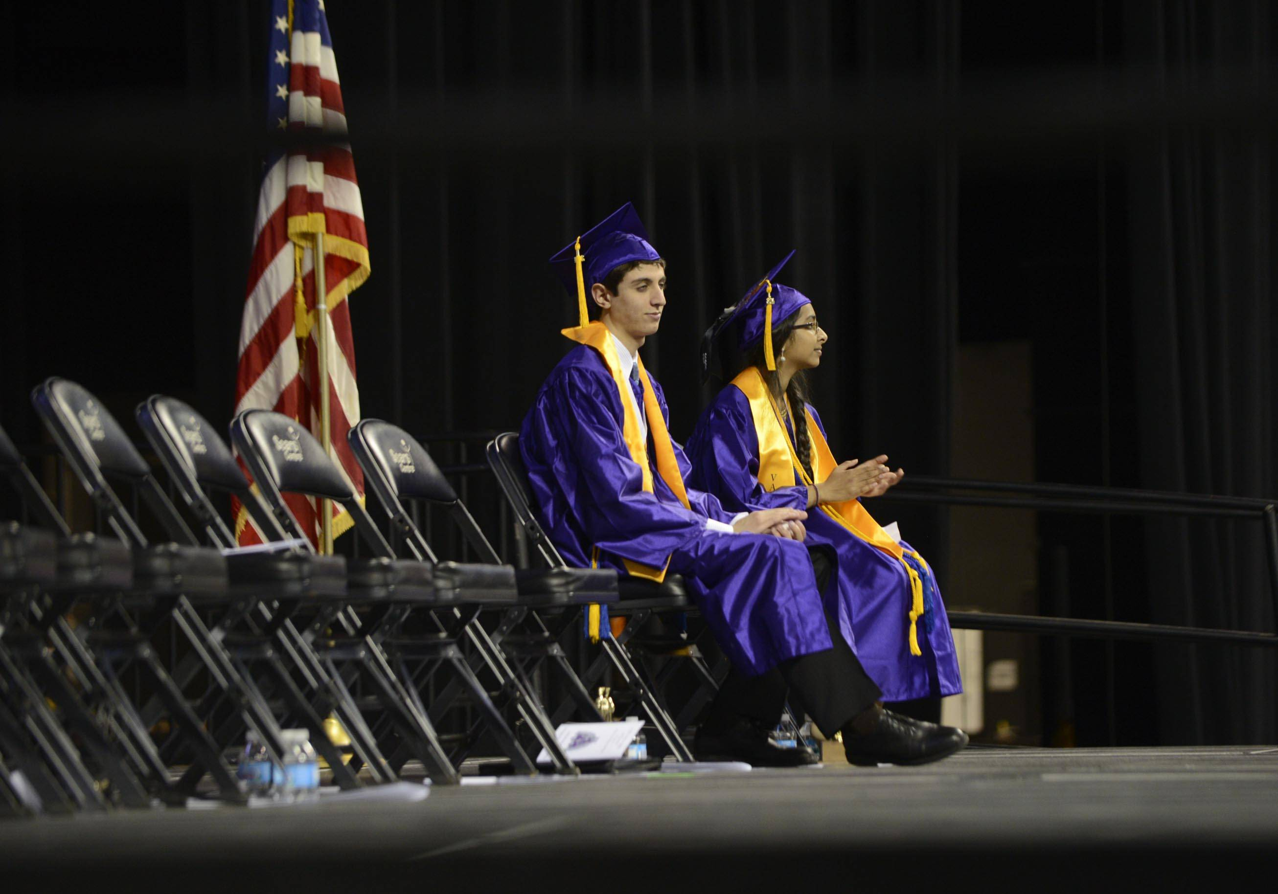 Salutatorian Mohammad Rashed and Valedictorian Shruti Kansara sit alone on stage as their classmates receive their diplomas Saturday at the Hampshire High School 2014 Commencement at the Sears Center in Hoffman Estates.