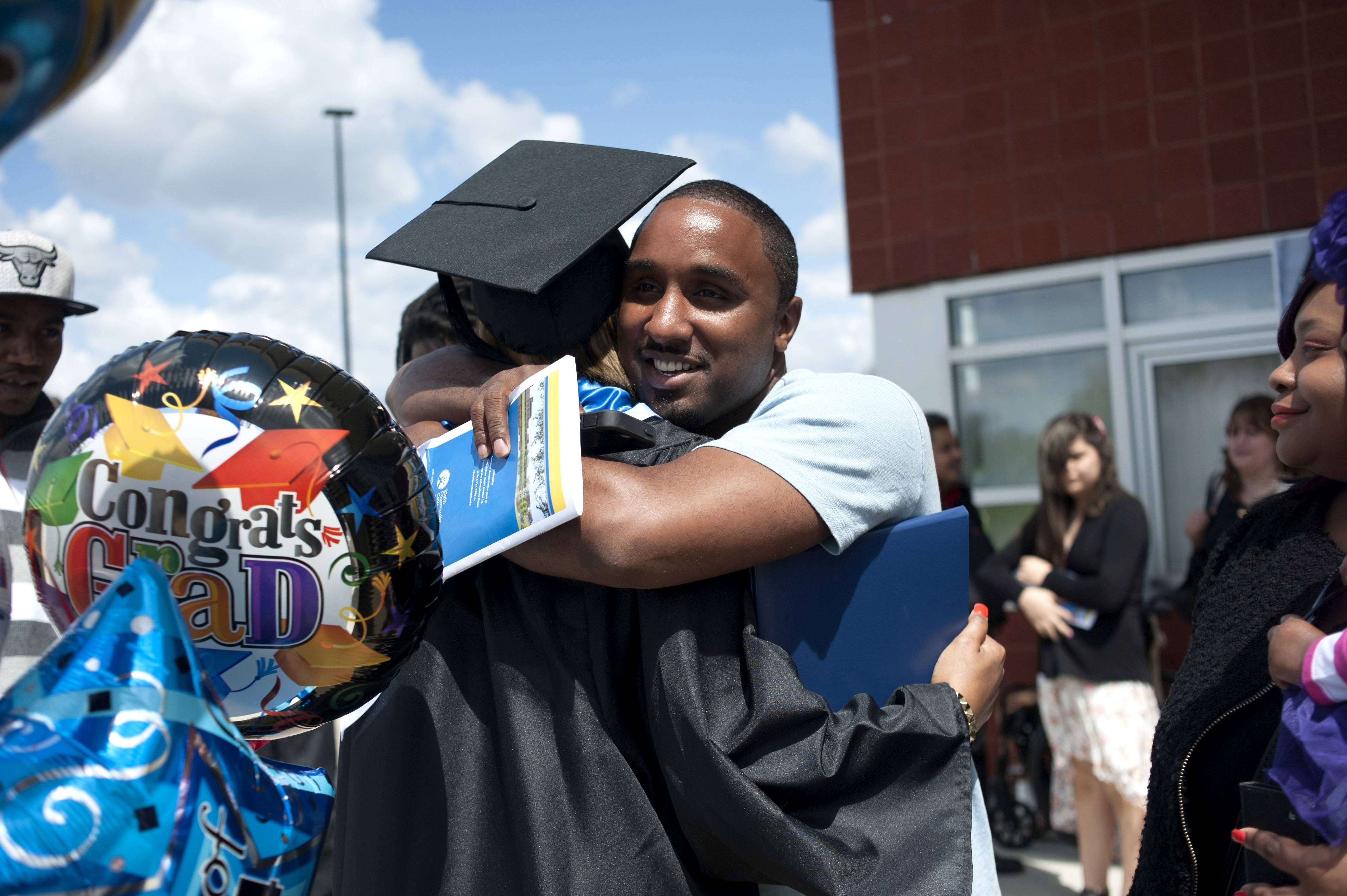 Stefan Sellers hugs his sister Candace after the Elgin Community College commencement outside the Spartan Events Center on Saturday. Sellers earned an associate in arts degree.
