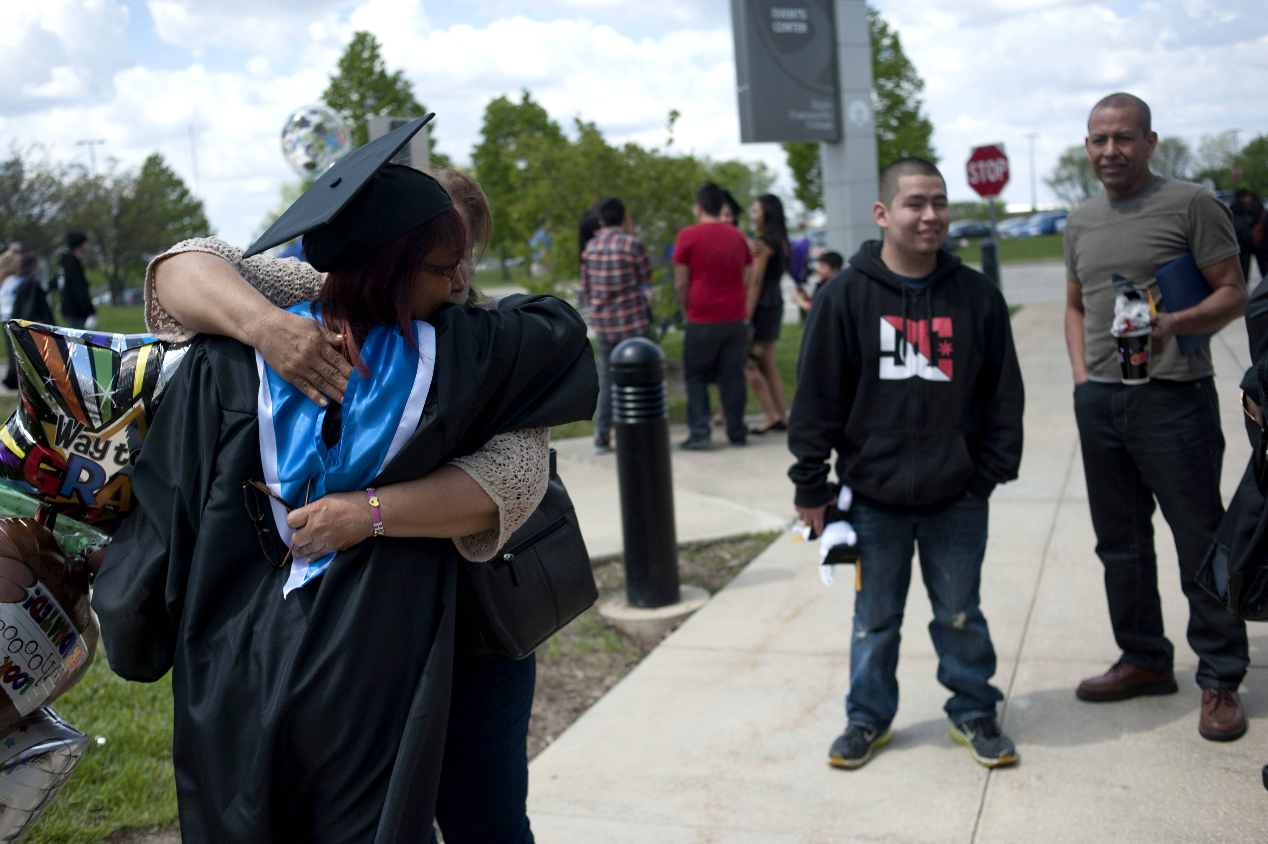 Virginia Garcia is greeted by her family after the Elgin Community College commencement outside the Spartan Events Center on Saturday. Garcia earned an associate in science degree.