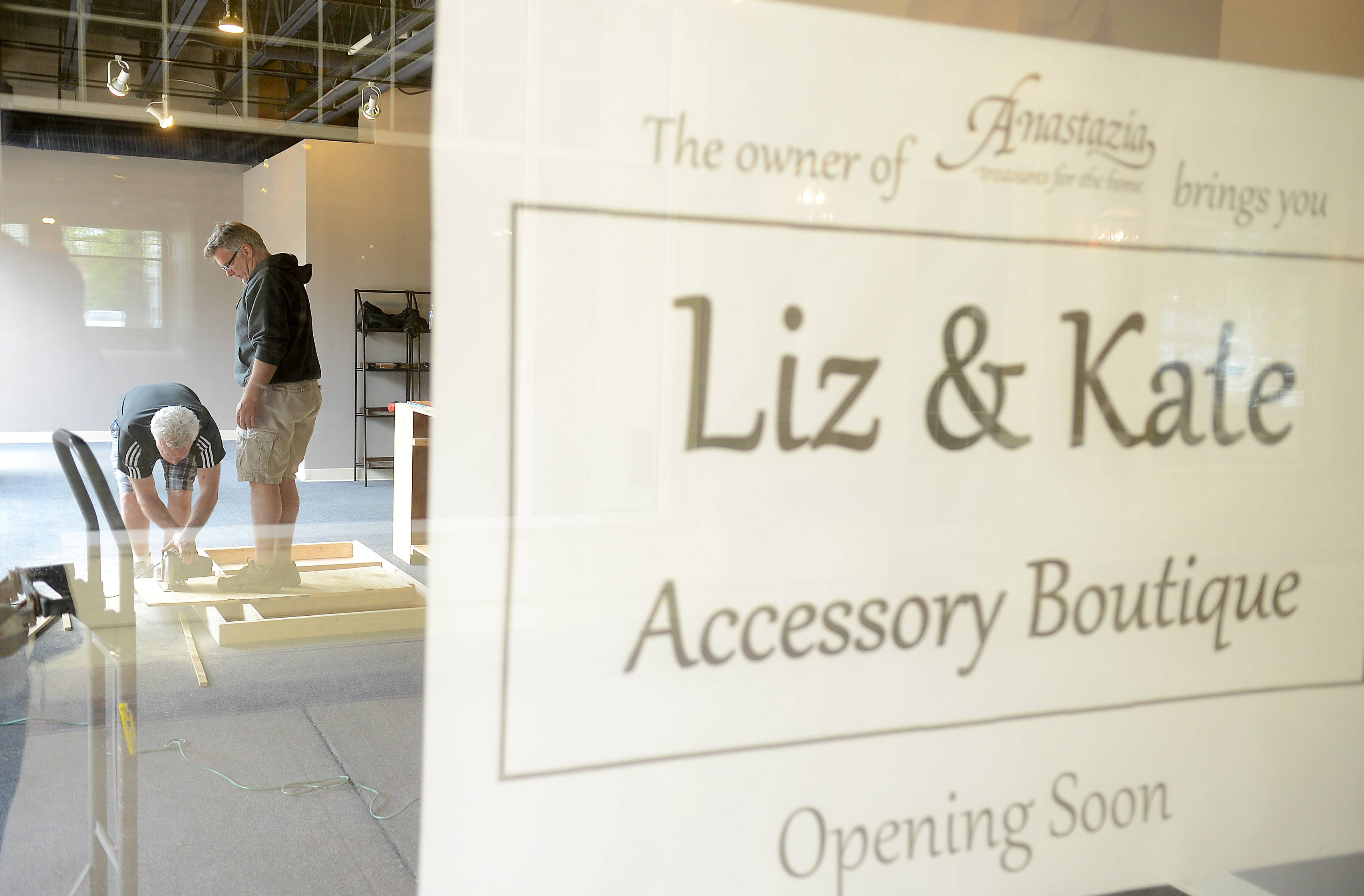 Owner Tom Konopacki, right, works with his brother Paul as they ready Liz & Kate Accessory Boutique to open in Dodson Place in Geneva. The store is a spinoff of home decor store Anastazia, and it basically moves the jewelry, handbags, scarves and other accessories into their own shop.
