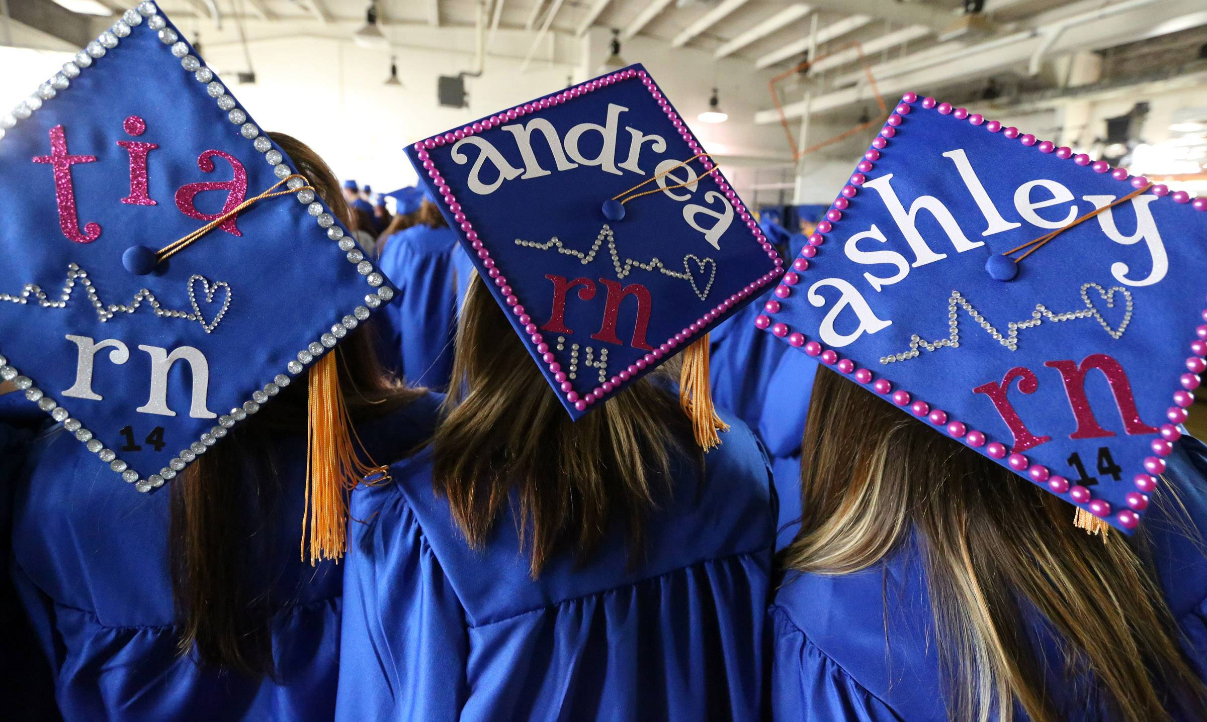 Tia Echterling of Antioch, left to right, Andrea Miculinich of Volo, and Ashley Besler of Lake Villa wait in line before College of Lake County's 45th commencement ceremony on Saturday in Grayslake.