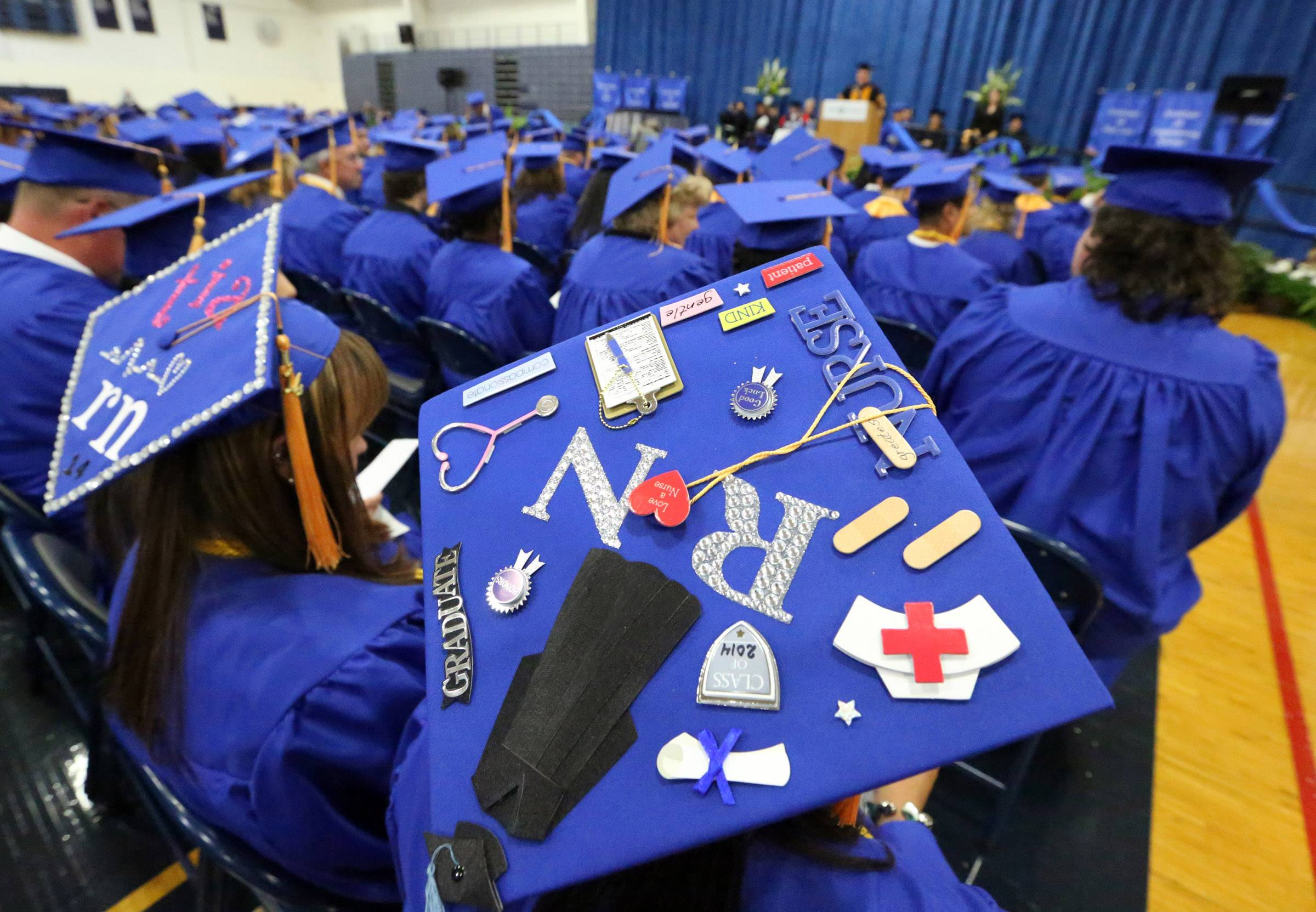 Tia Echterling of Antioch, left, and Lashuan Davis of Zion wear decorated caps during College of Lake County's 45th commencement ceremony on Saturday in Grayslake.