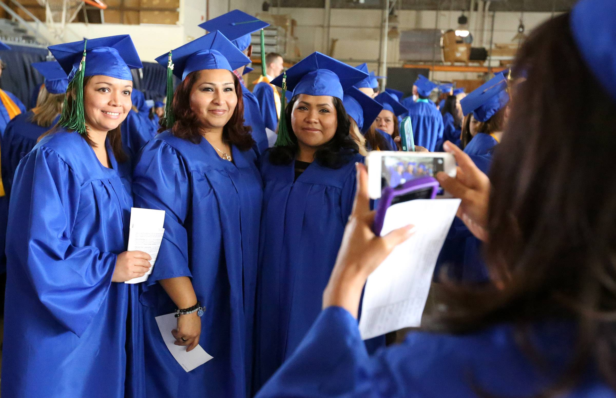 Aleyda Casas of Round Lake takes a photo of friends Maria Quinones of Grayslake, left to right, Araceli Torres of Round Lake, and Maria Sanchez of Zion before College of Lake County's 45th commencement ceremony on Saturday in Grayslake.