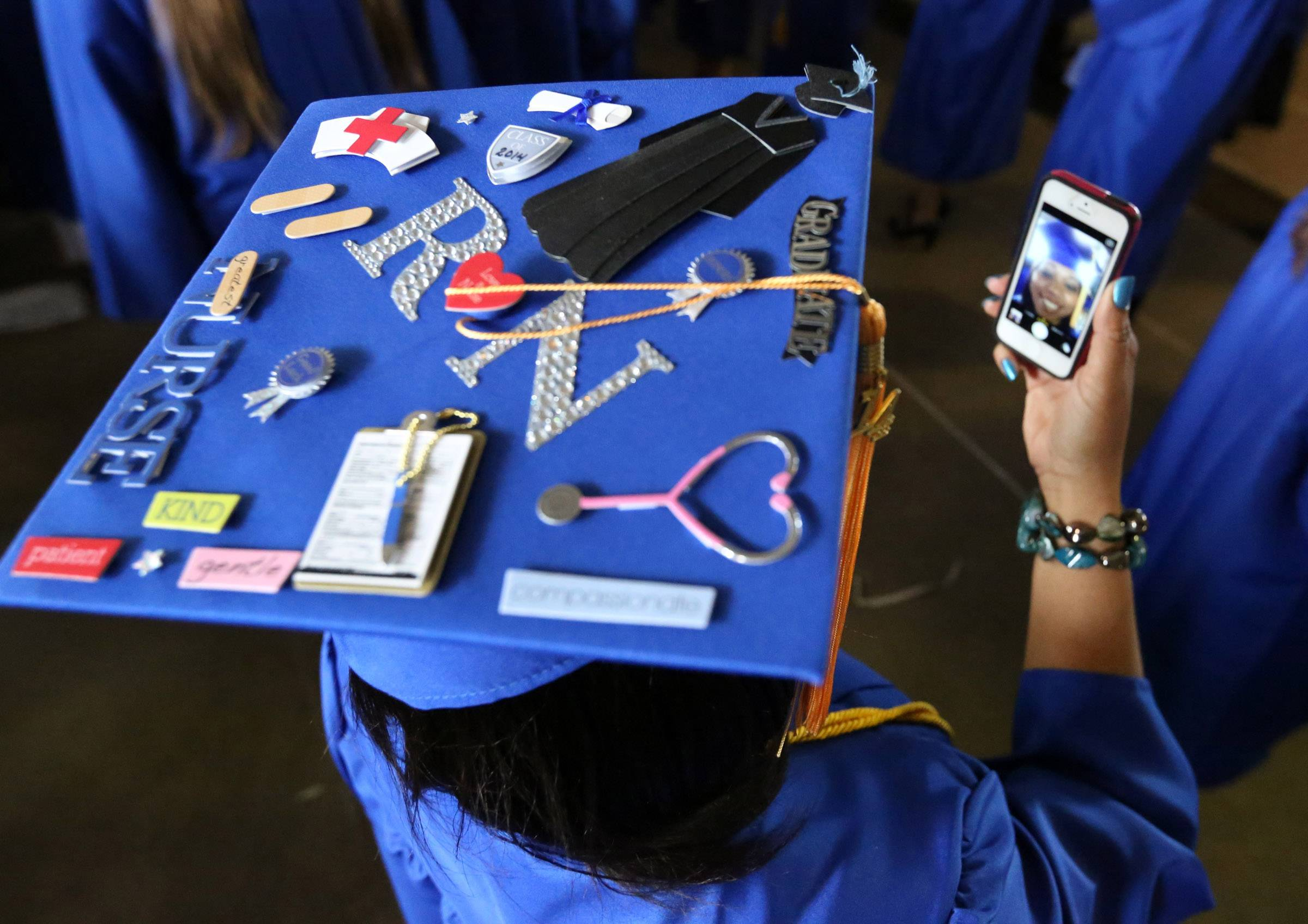 Lashuan Davis of Zion looks at her cellphone to change her decorated cap position before College of Lake County's 45th commencement ceremony on Saturday in Grayslake.