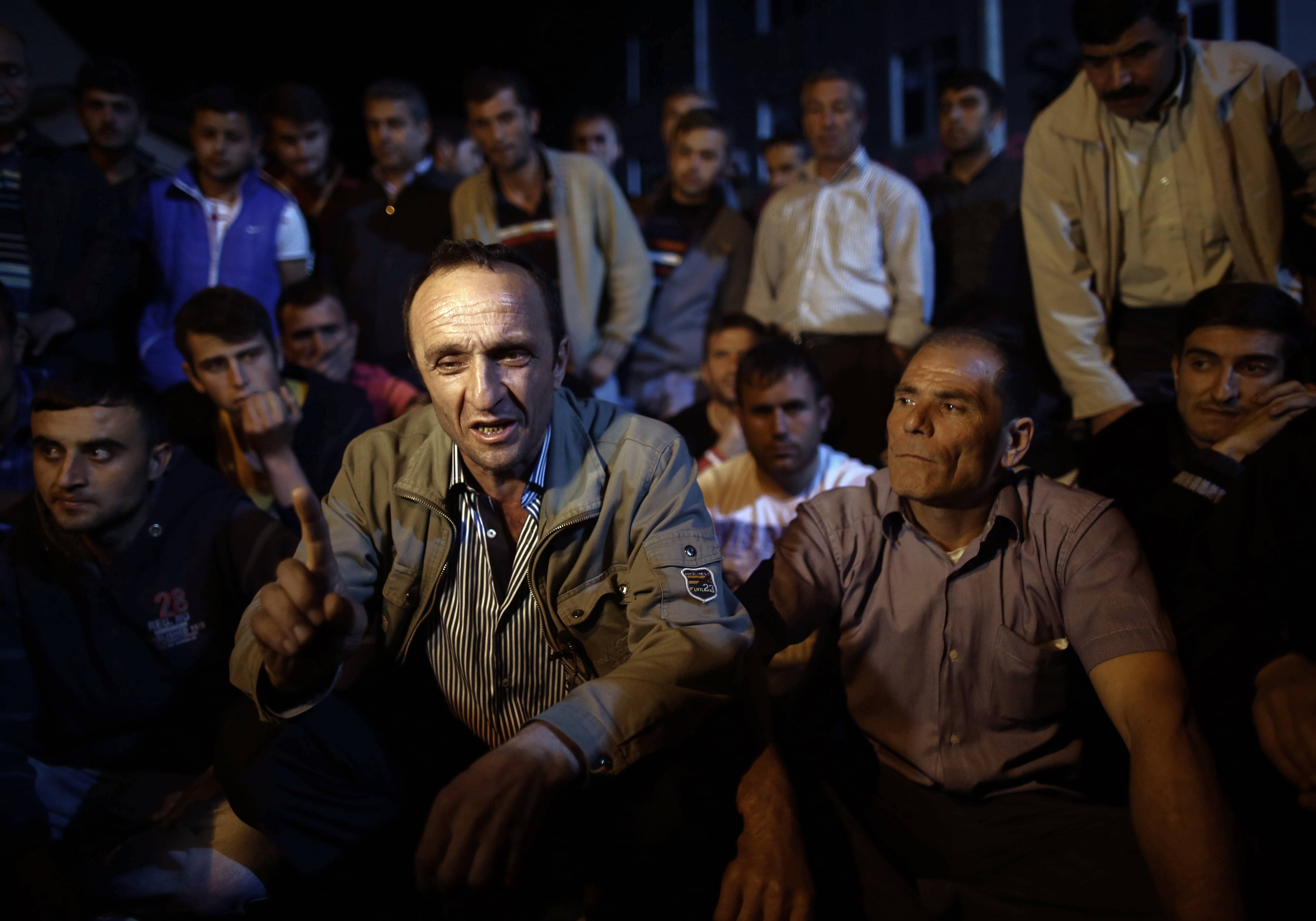 Miner Cetin Esmer speaks to the Associated Press as he joined fellow miners and their children to commemorate the Soma mine accident victims and protest the government's labor policy in Savastepe , Turkey, late Friday.