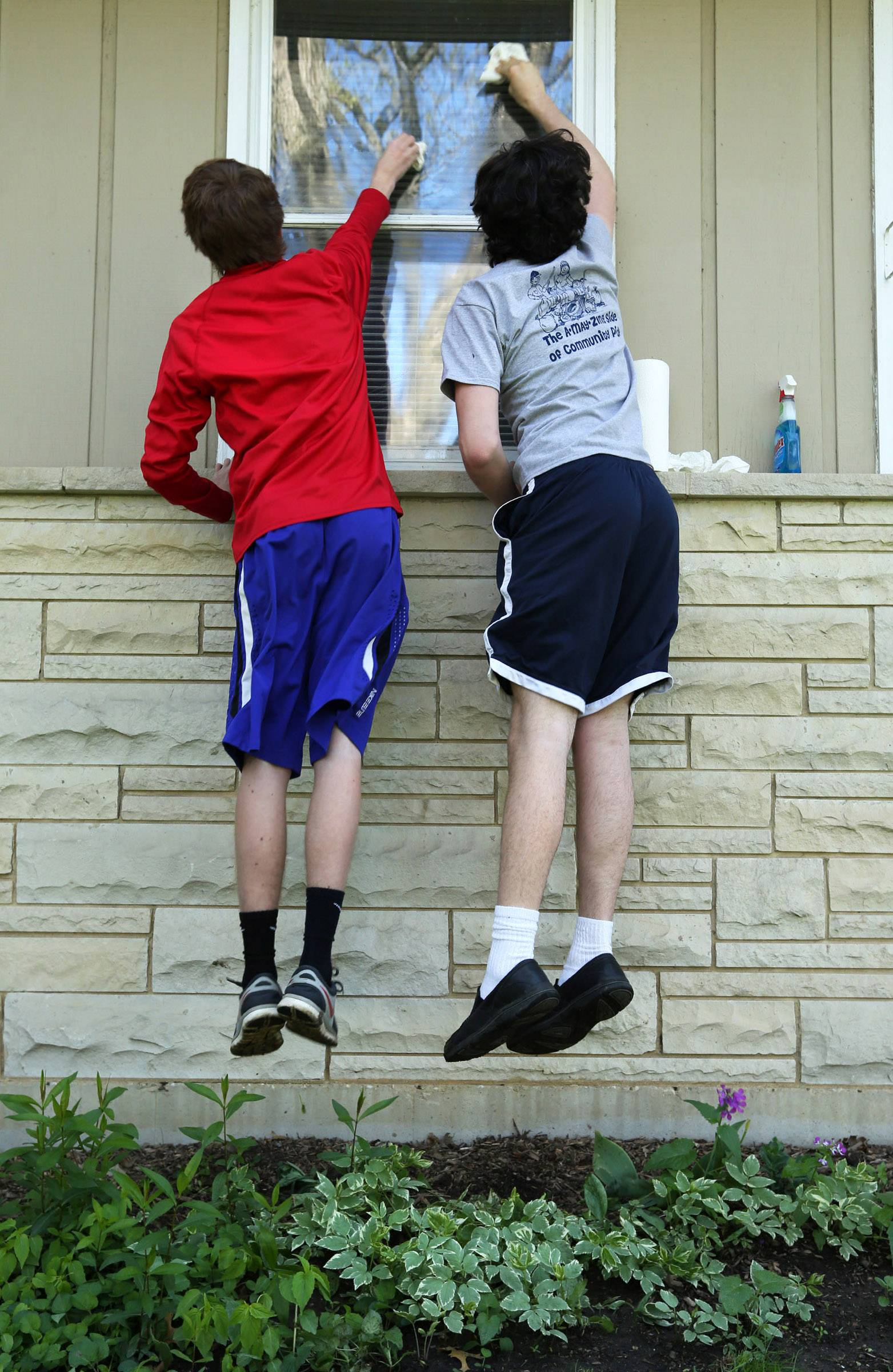Carmel High School students Matt Pomierski, left, and Brendan Higgins, both 17 of Libertyville, jump to clean the top part of a side window at Agnes Radakovitz' house in Mundelein as part of the Village of Mundelein's annual A-May-Zing event on Saturday.