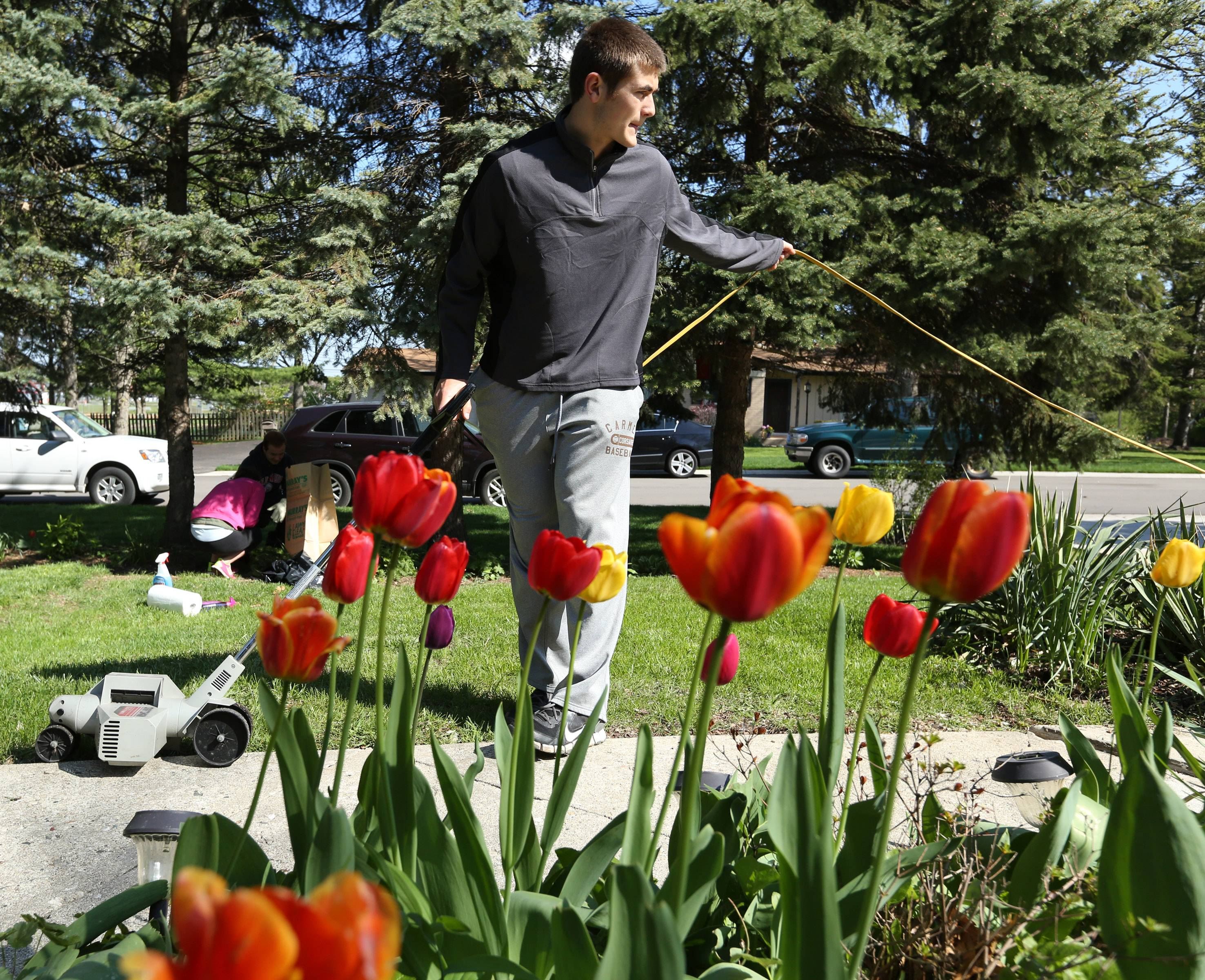 Carmel High School student Joe Hoy, 17, edges the sidewalk at Agnes Radakovitz' house in Mundelein as part of the Village of Mundelein's annual A-May-Zing event on Saturday.