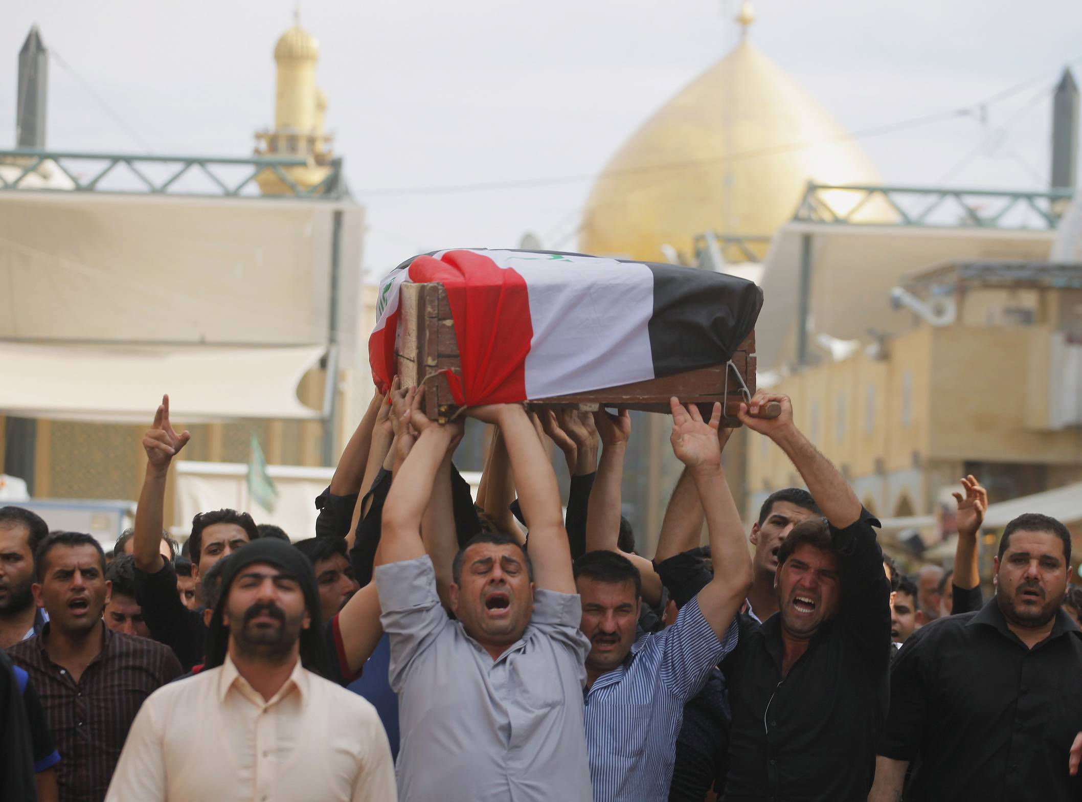 Mourners chant slogans against the al-Qaida breakaway group Islamic State of Iraq and the Levant (ISIL), while carrying a flag-draped coffin of Ahmed Marzouk an Iraqi officer who was killed, said his family, in a fake checkpoint on Thursday, during his funeral procession in the Shiite holy city of Najaf, 100 miles south of Baghdad, Iraq, Friday, May 16, 2014.
