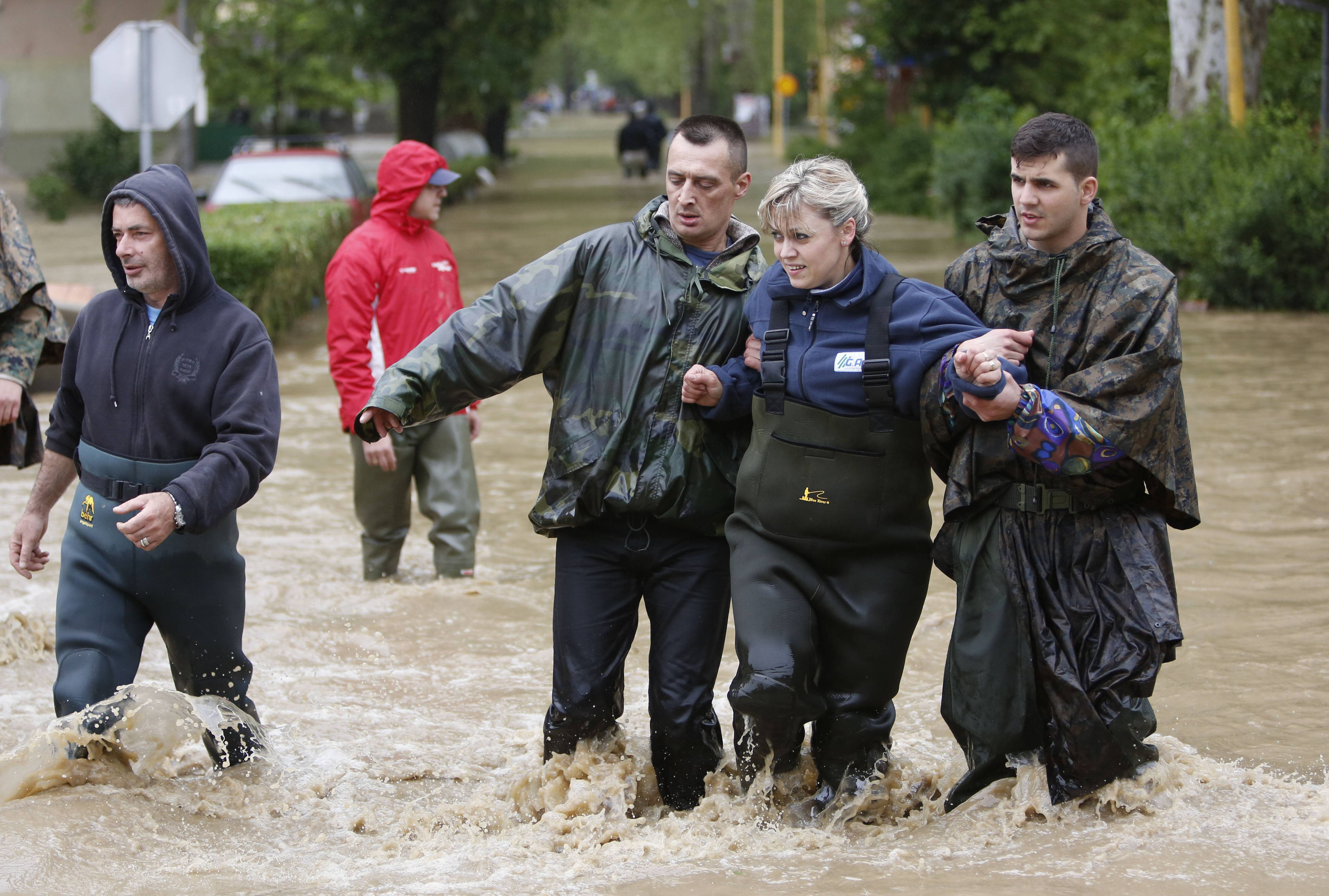 Members of the Bosnian army rescue a woman stranded in her home due to flooding,  in the Bosnian town of Maglaj, 150 kms north of Sarajevo, Friday May 16, 2014.