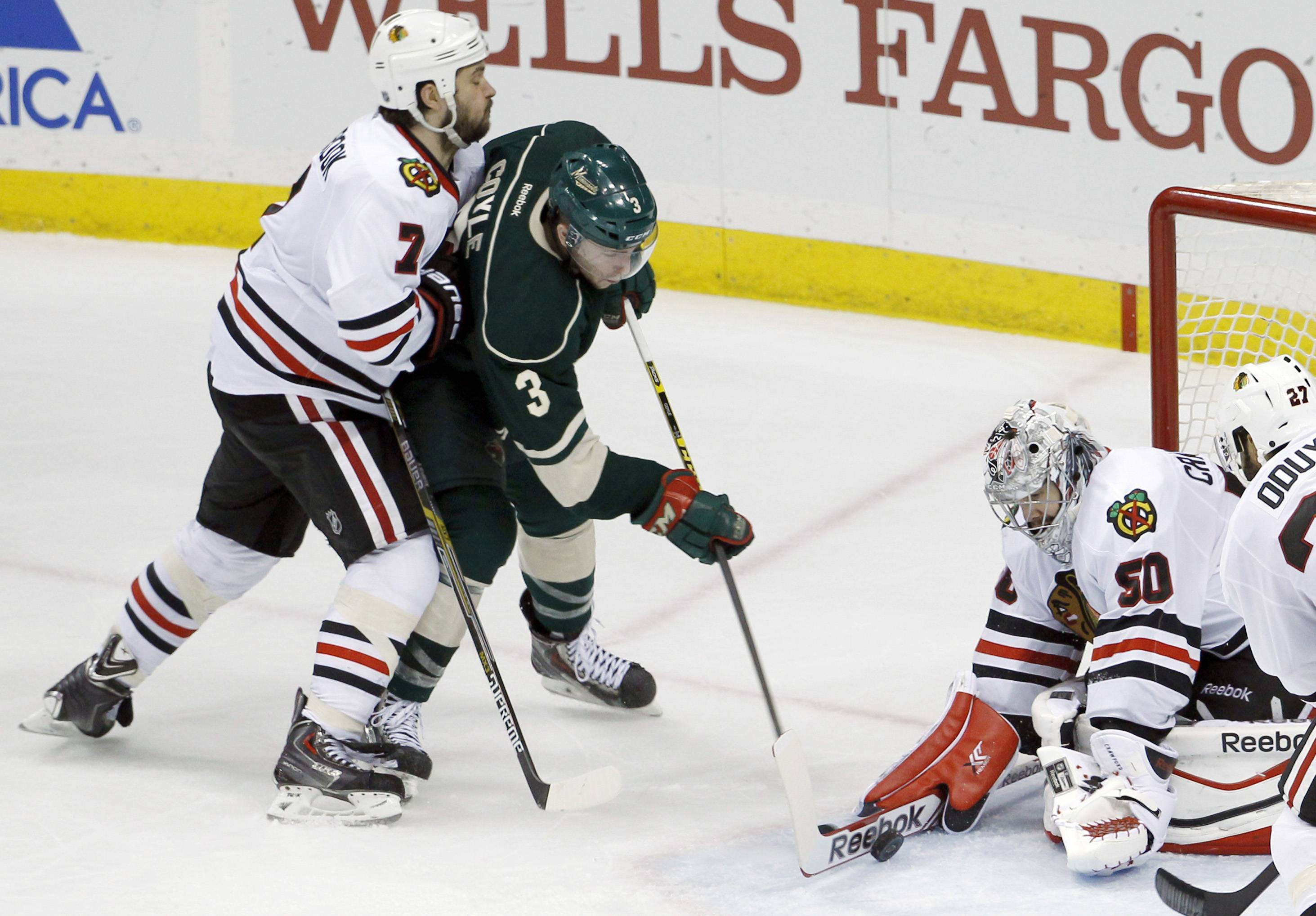 Blackhawks goalie Corey Crawford (50) scoops away a shot by Minnesota Wild center Charlie Coyle (3) as Blackhawks defenseman Brent Seabrook (7) pressures Coyle during the third period of Game 6 of an NHL hockey second-round playoff series in St. Paul, Minn., Tuesday, May 13, 2014. The Blackhawks won 2-1 in overtime.