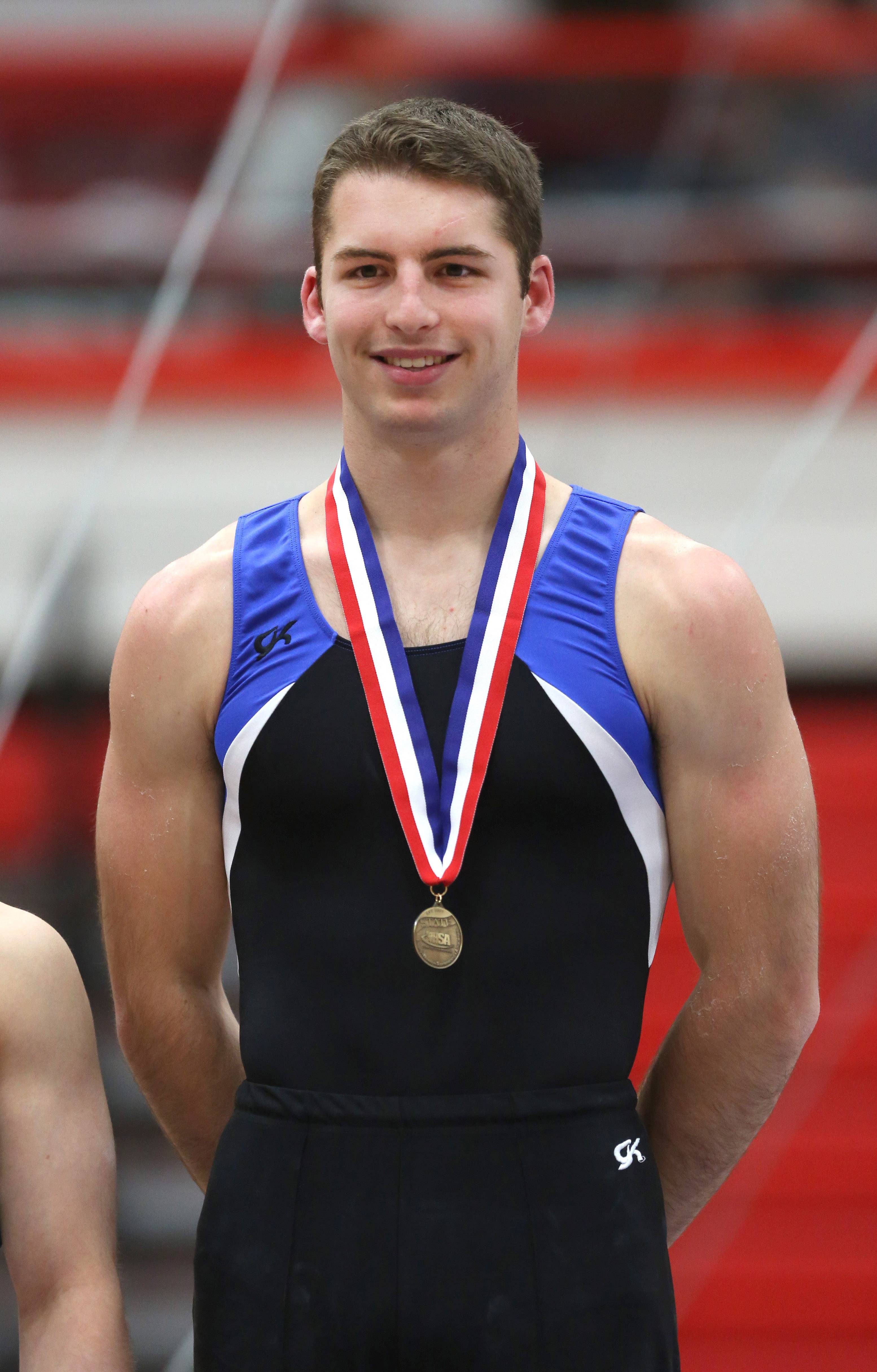 Wheaton Warrenville co-op's David MacDonald gets comfortable on the winners stand during the state boys gymnastics finals Saturday at Hinsdale Central.