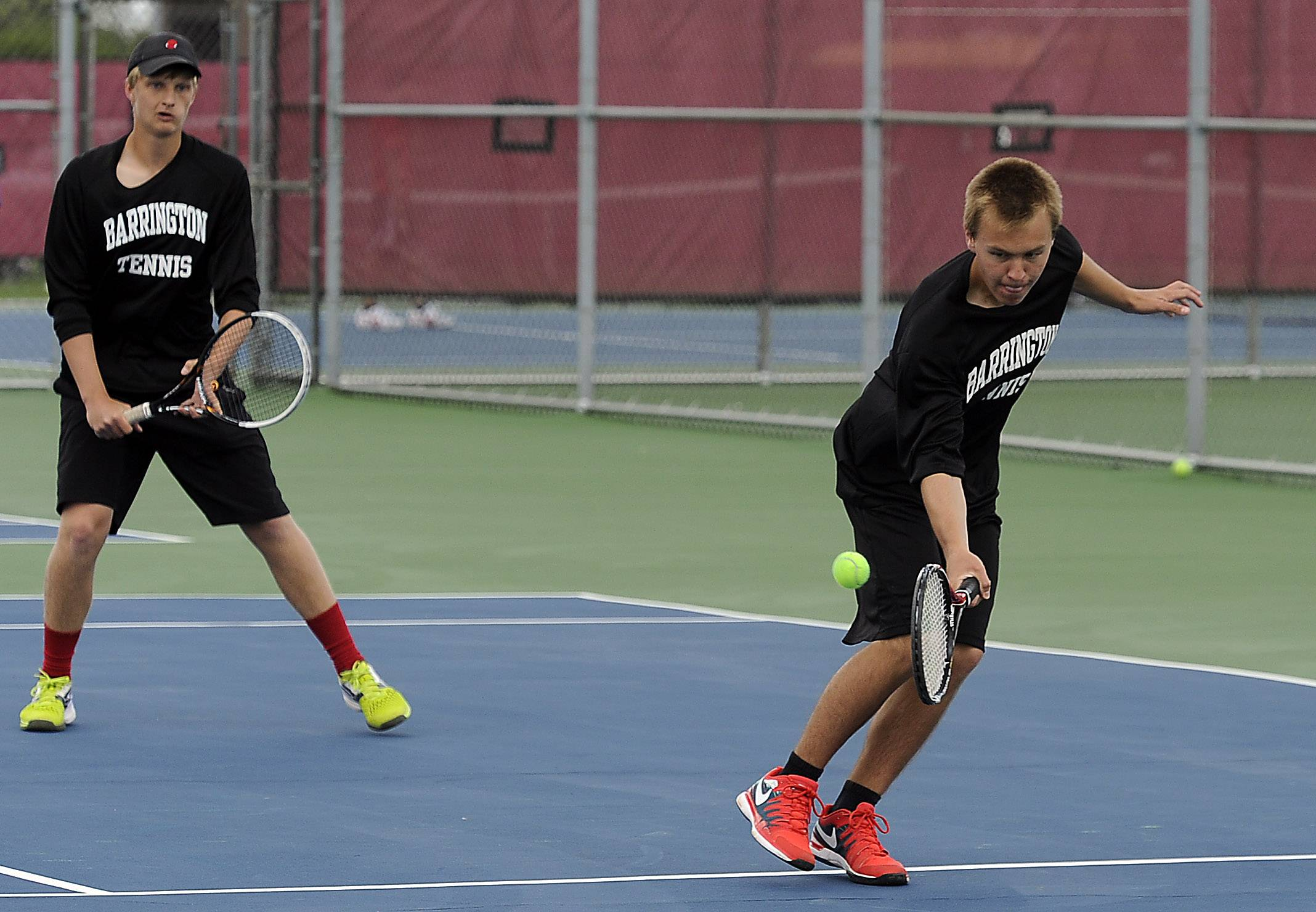 Barrington's Scott Apmann returns a low ball as his doubles partner Dean Carlson looks on during Saturday's Mid-Suburban League touranment at Schaumburg.