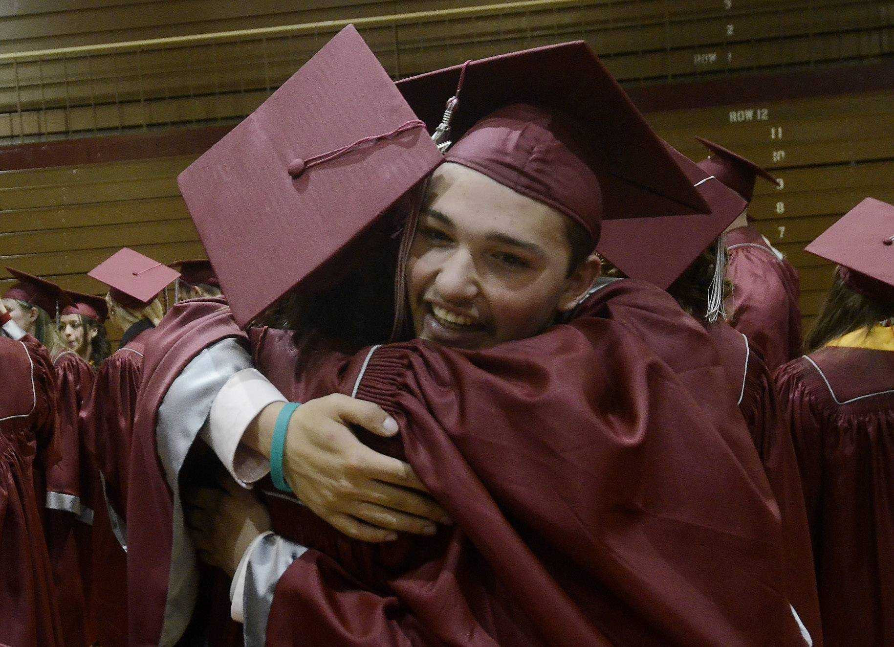 Tom Ruffolo gets a hug from Cindy Sanchez before the Antioch Community High School graduation on Sunday at the school.