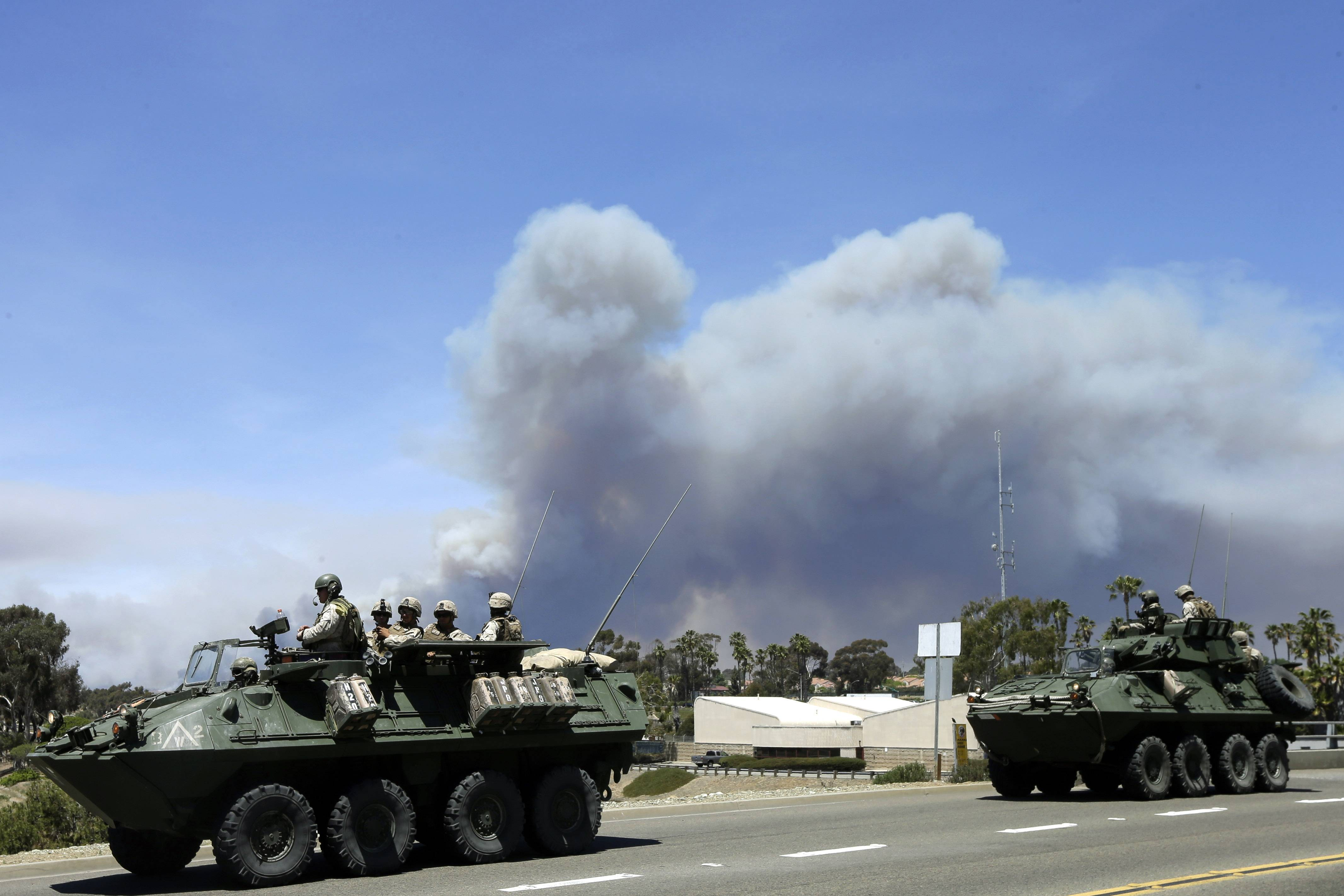 Marines move military vehicles near the entrance to Marine Corps Camp Pendleton in front of smoke plumes from the Las Pulgas wildfire burning on the base last week.