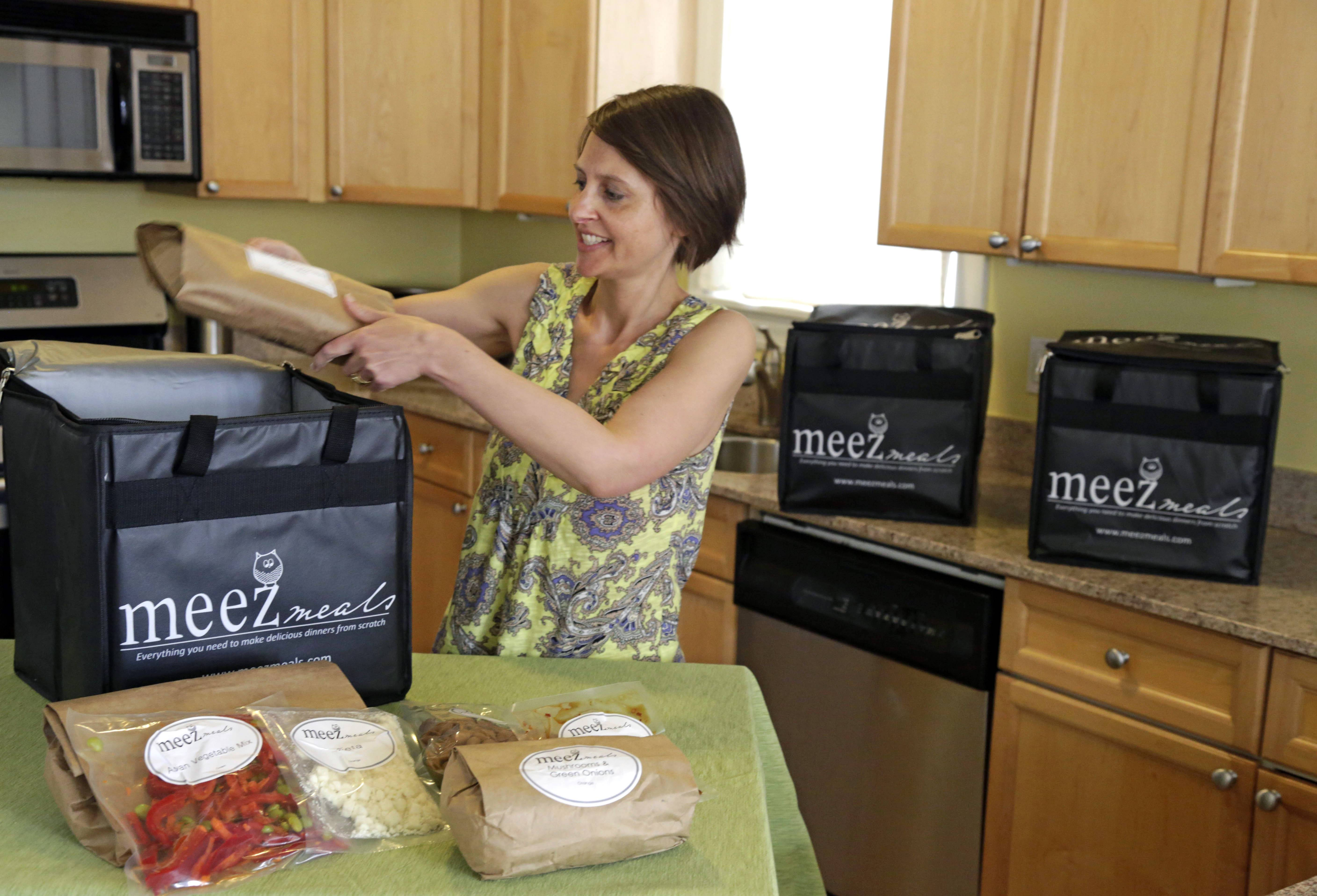 Jen Collins Moore, owner of Meez Meals, places some of her ready to cook entrées in a delivery container in her kitchen in Chicago. Her company makes and delivers ingredients for dinner to customers whose busy lifestyles leave little time for meal preparation.