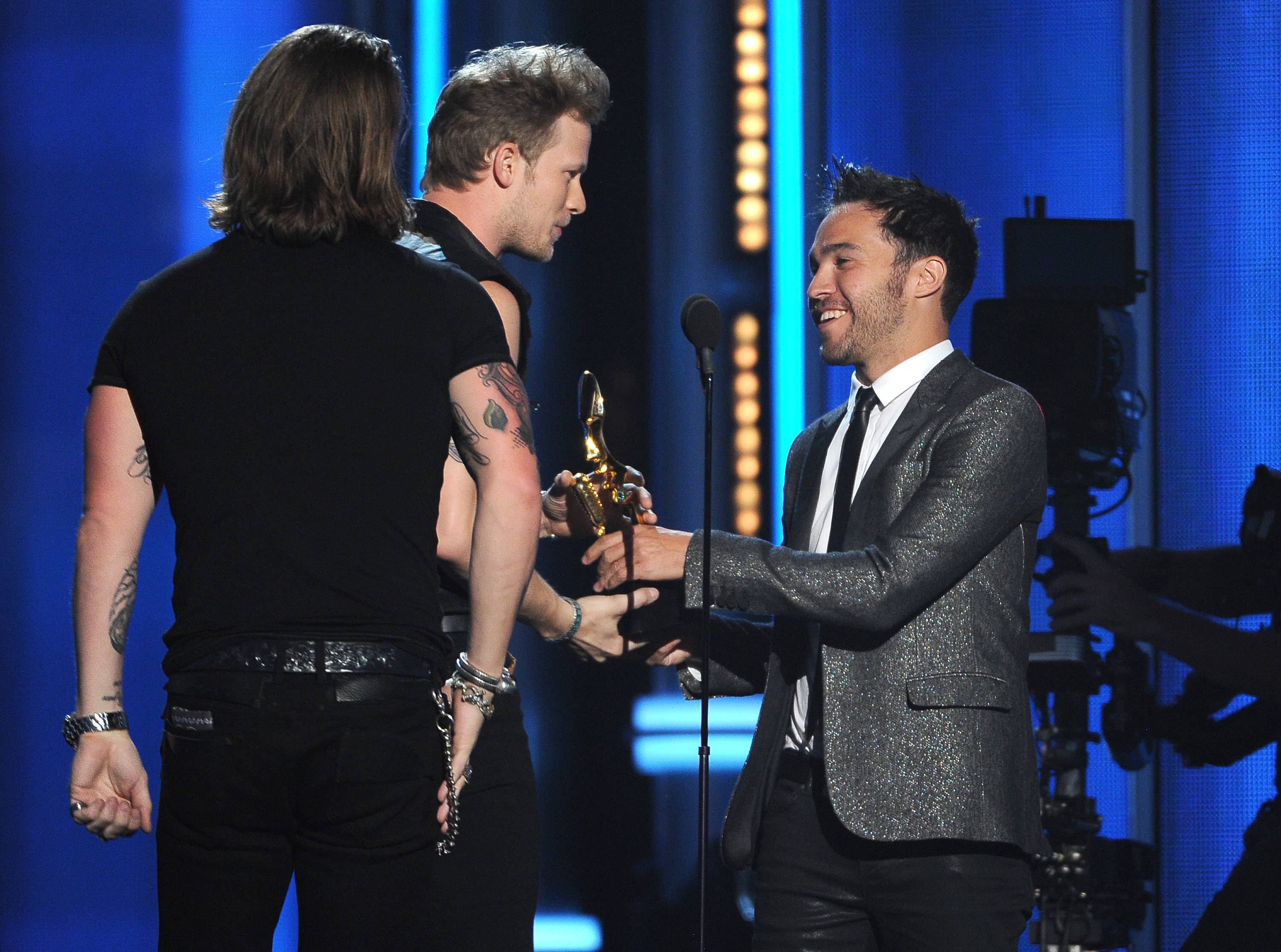 "Pete Wentz, right, presents the award for top country song to Tyler Hubbard, left, and Brian Kelley, of the musical group Florida Georgia Line for ""Cruise"" at the Billboard Music Awards at the MGM Grand Garden Arena on Sunday, May 18, 2014, in Las Vegas."