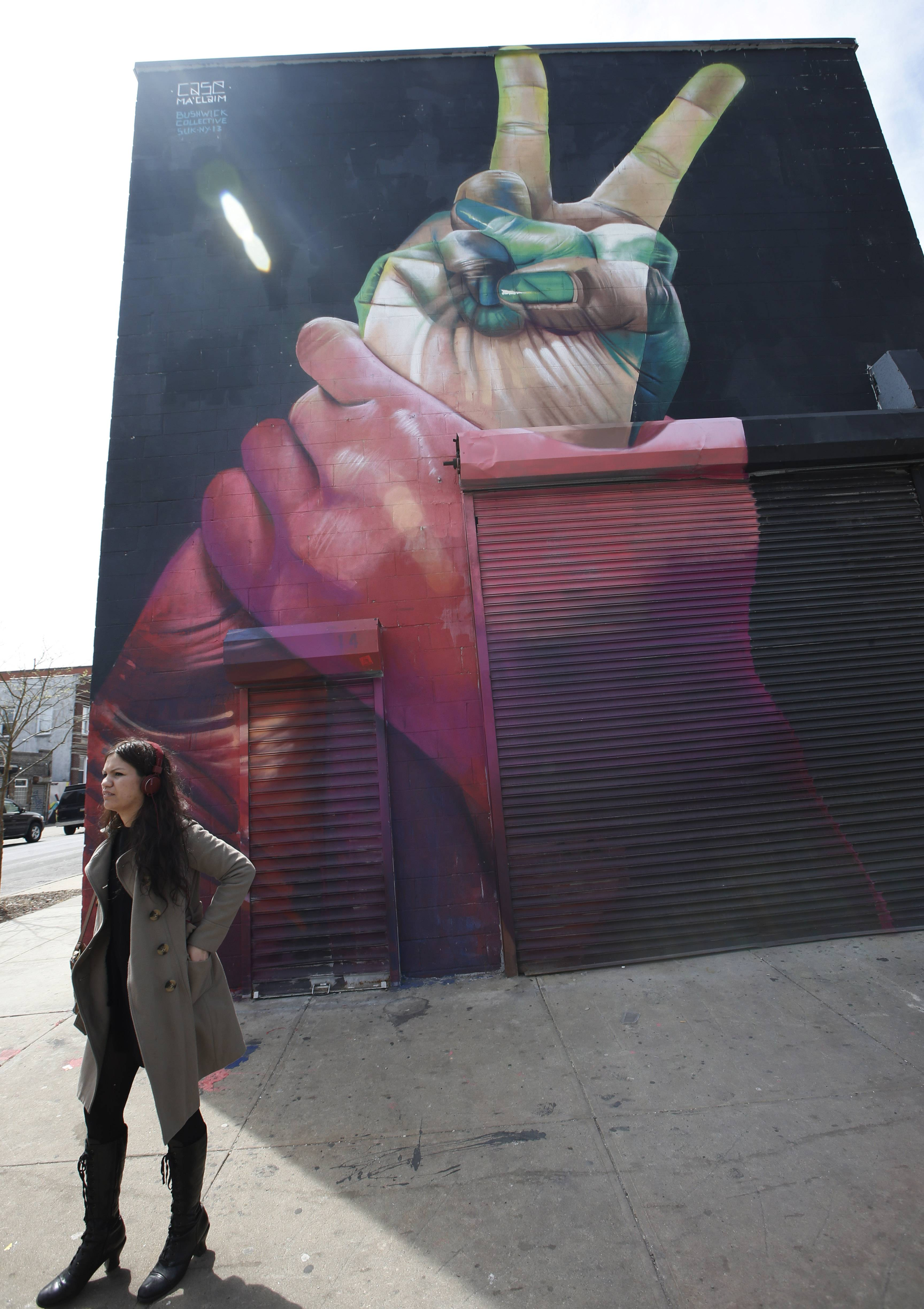 A young woman stands at the intersection of Wyckoff and Troutman streets against the backdrop of bold and colorful street art in Bushwick, New York.