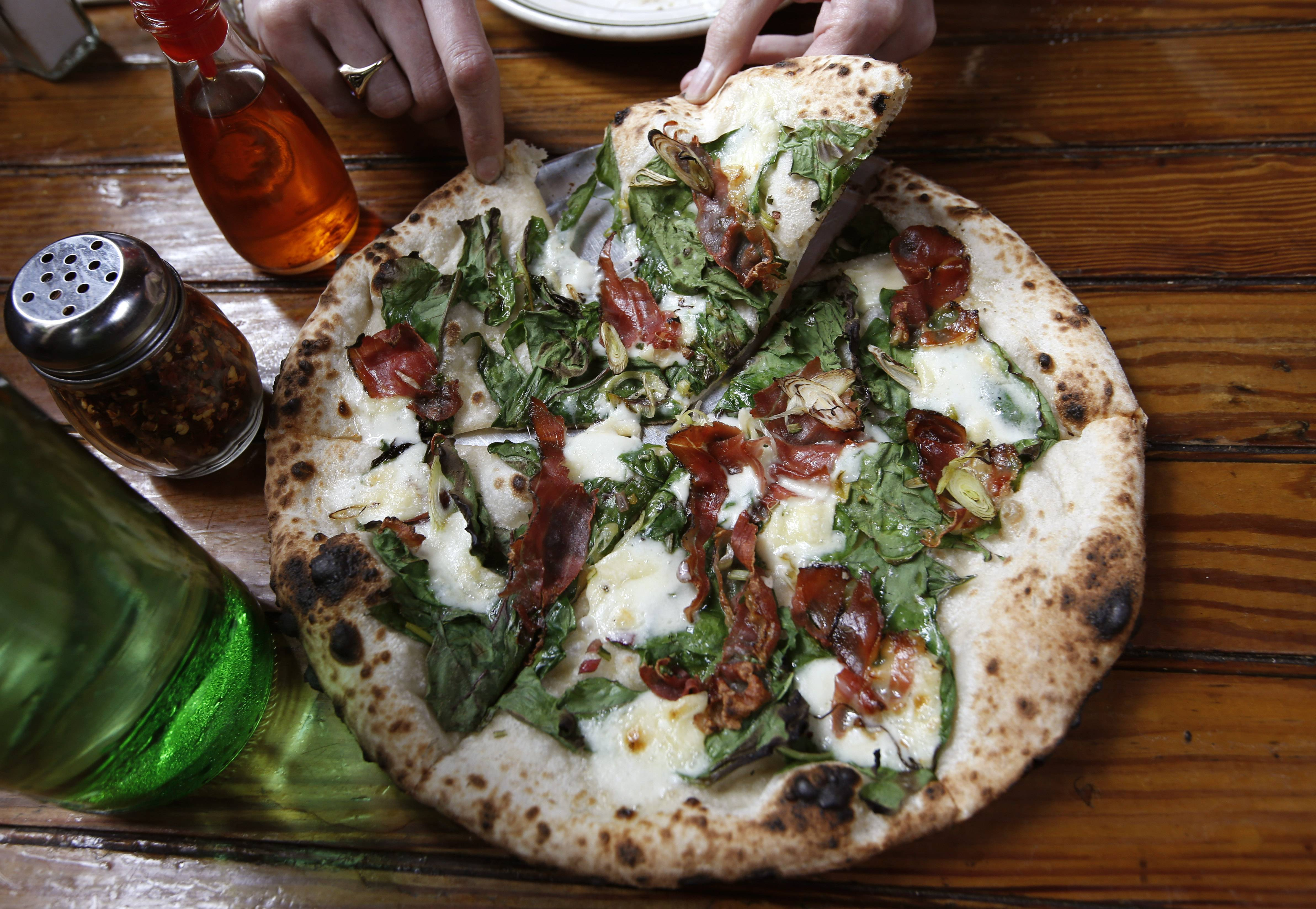 "A customer enjoys a slice of ""Tanya Charding"" thin-crust pizza, featuring Swiss chard, speck (a cured meat) and Robiola cheese, at Roberta's, the most-well-known of many new restaurants in the emerging Bushwick neighborhood in New York."