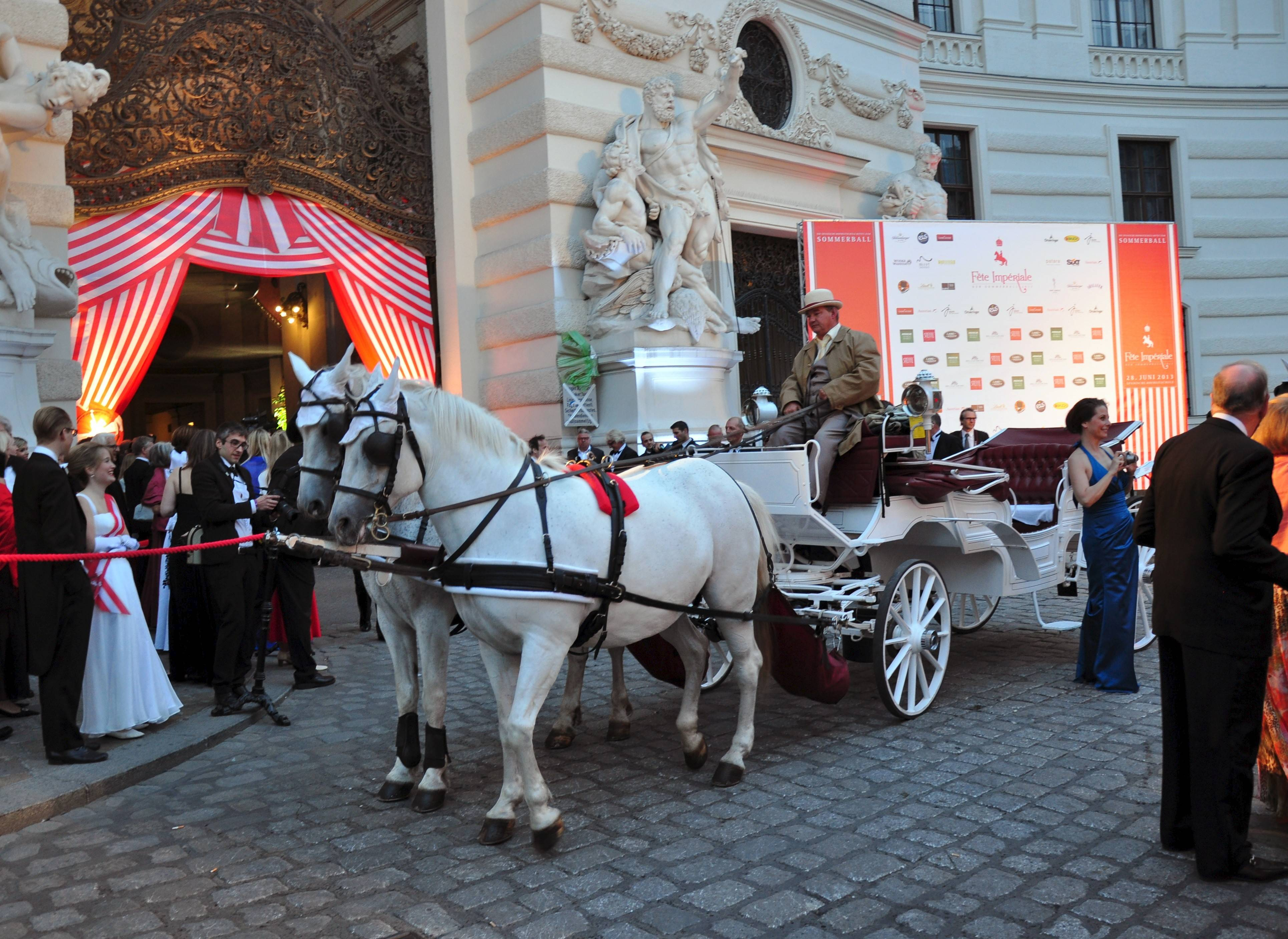 Horse-drawn carriages transport ball goers to the Hofburg Palace for the Fete Imperiale in Vienna, Austria.