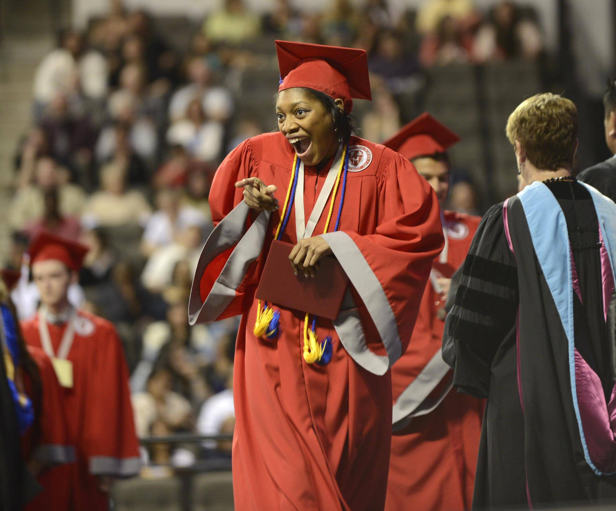 Graduate Chamaya Moody gestures toward a video camera as she crosses the stage with her diploma Sunday at the Mundelein High school Commencement Exercises at Sears Center in Hoffman Estates.