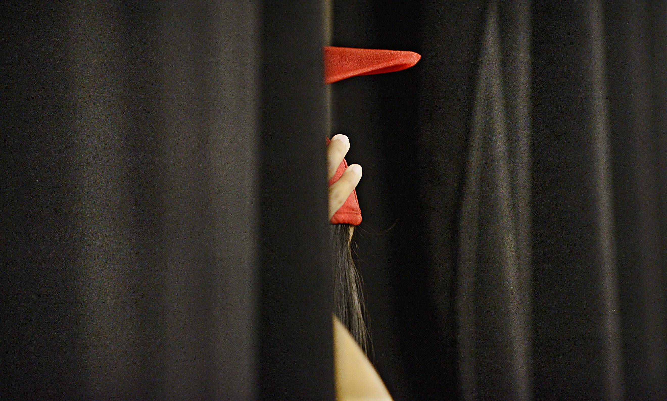 Graduate Brenda Abrego makes a final adjustment to her mortarboard as she waits with classmates behind a black curtain Sunday before the Mundelein High school Commencement Exercises at Sears Center in Hoffman Estates.