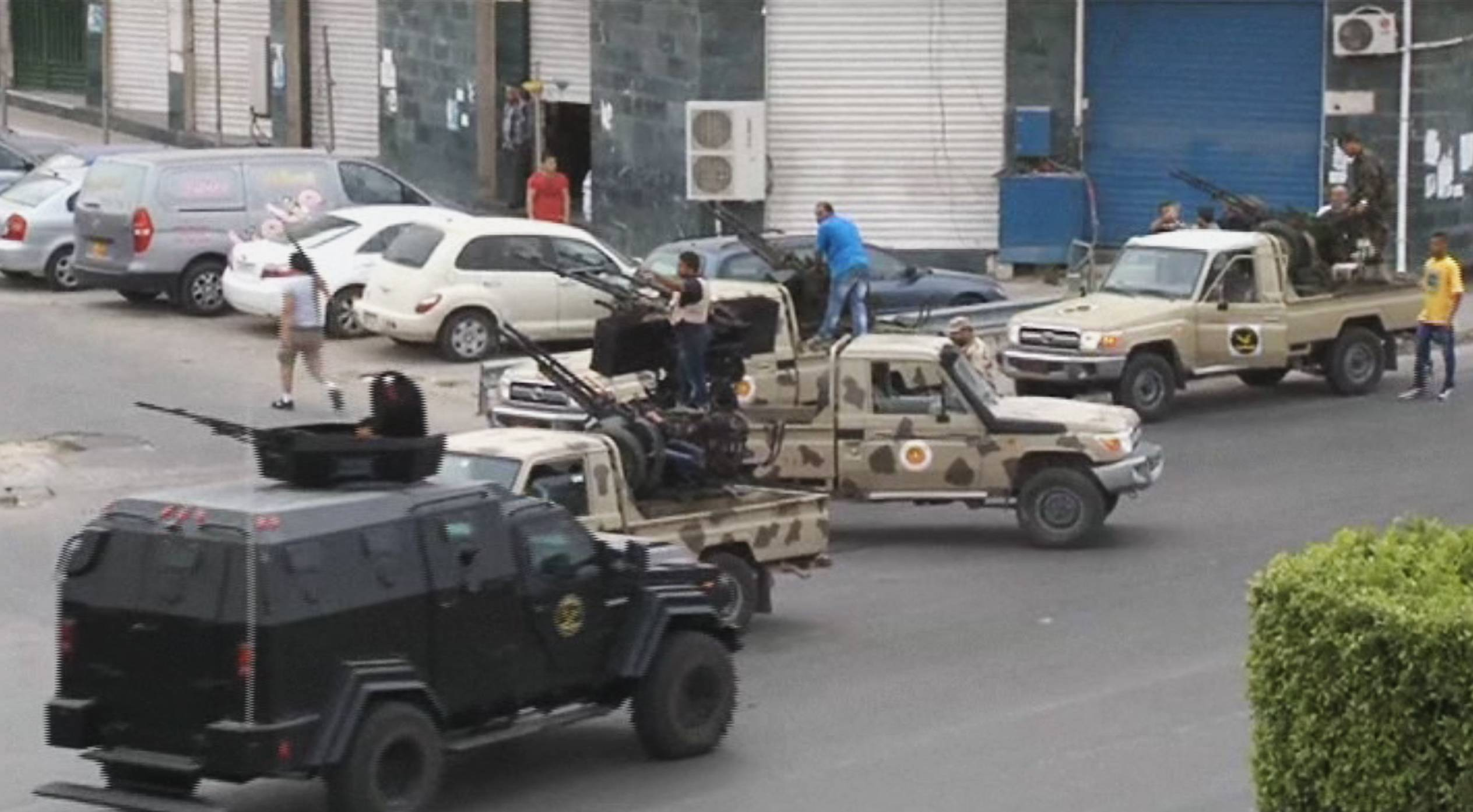 In this image made from video provided by the Libyan national army via AP Television, Tripoli joint security forces on vehicles with heavy artillery stand guard on the entrance road to the parliament area after troops of Gen. Khalifa Hifter targeted Islamist lawmakers and officials in Tripoli Sunday.