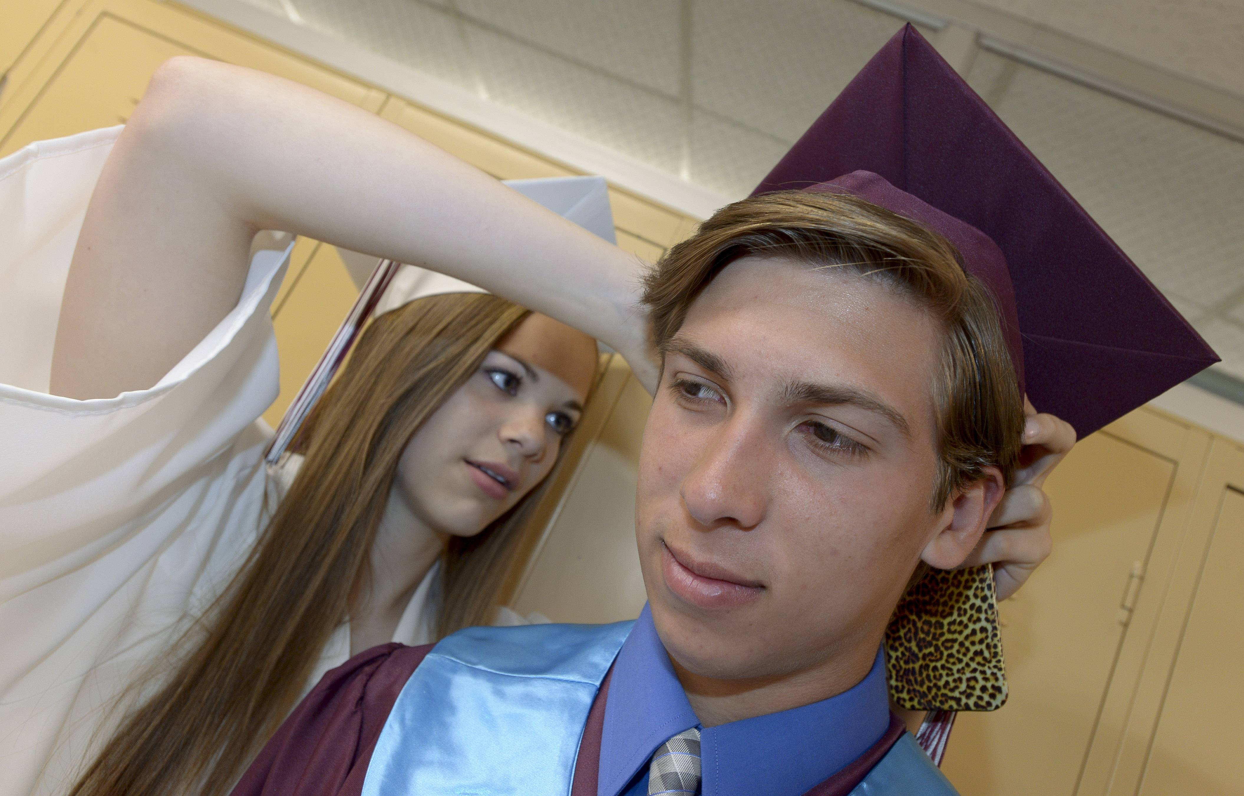 Kiera Johnston and Jimmy Clausing get ready for the Montini Catholic High School's graduation on Sunday, May 18, at Montini in Lombard.