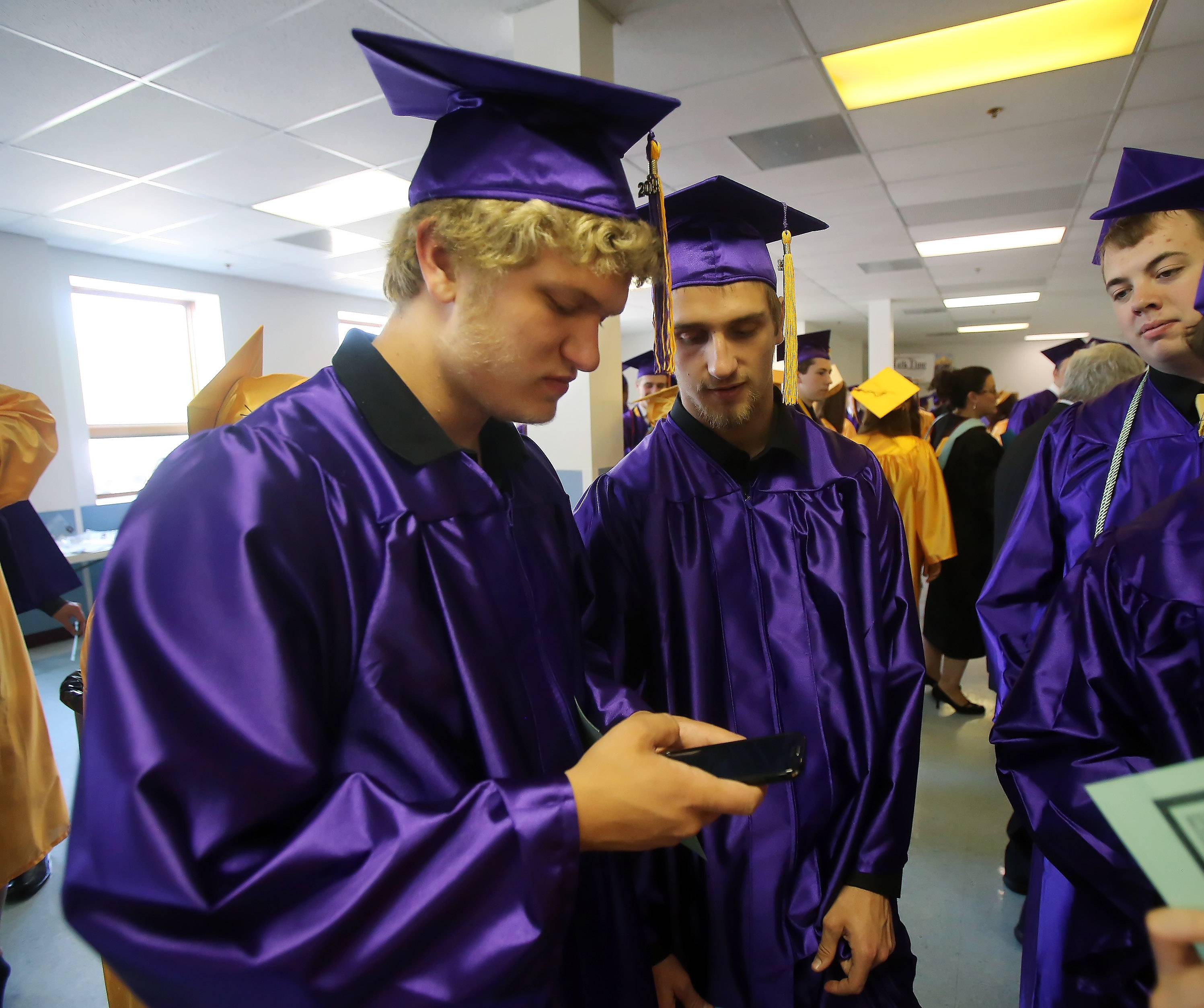 Luke Fugle, left, and Ben Kimlinger keep up with the Chicago Blackhawks playoff game during the 98th annual Wauconda High School graduation on Sunday at Quentin Bible Church in Lake Zurich. There were 289 graduates at this years commencement ceremony.