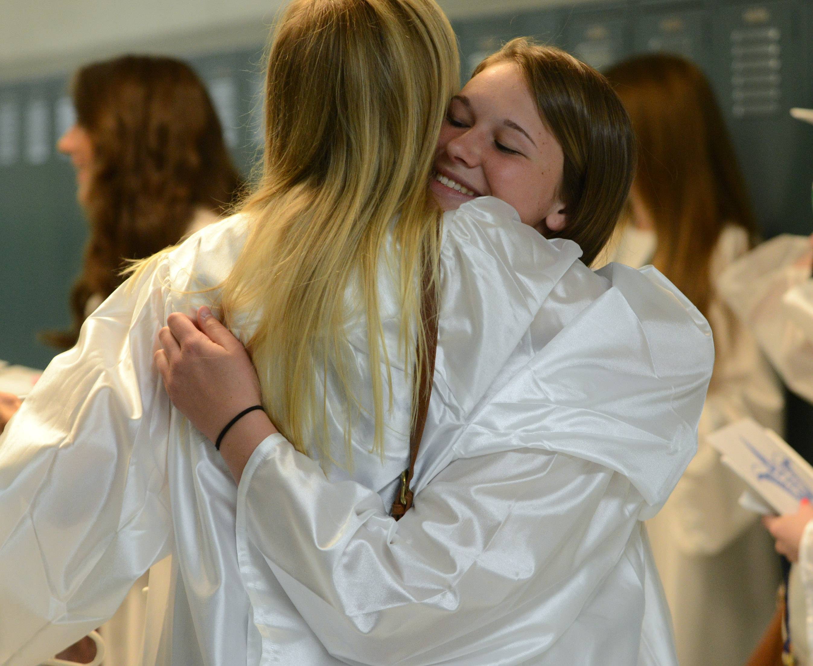 Grayslake Central High School's  Jamie Brew, right, shares a hug with Lexi Beckman before the start of Sunday's graduation ceremony at the school.