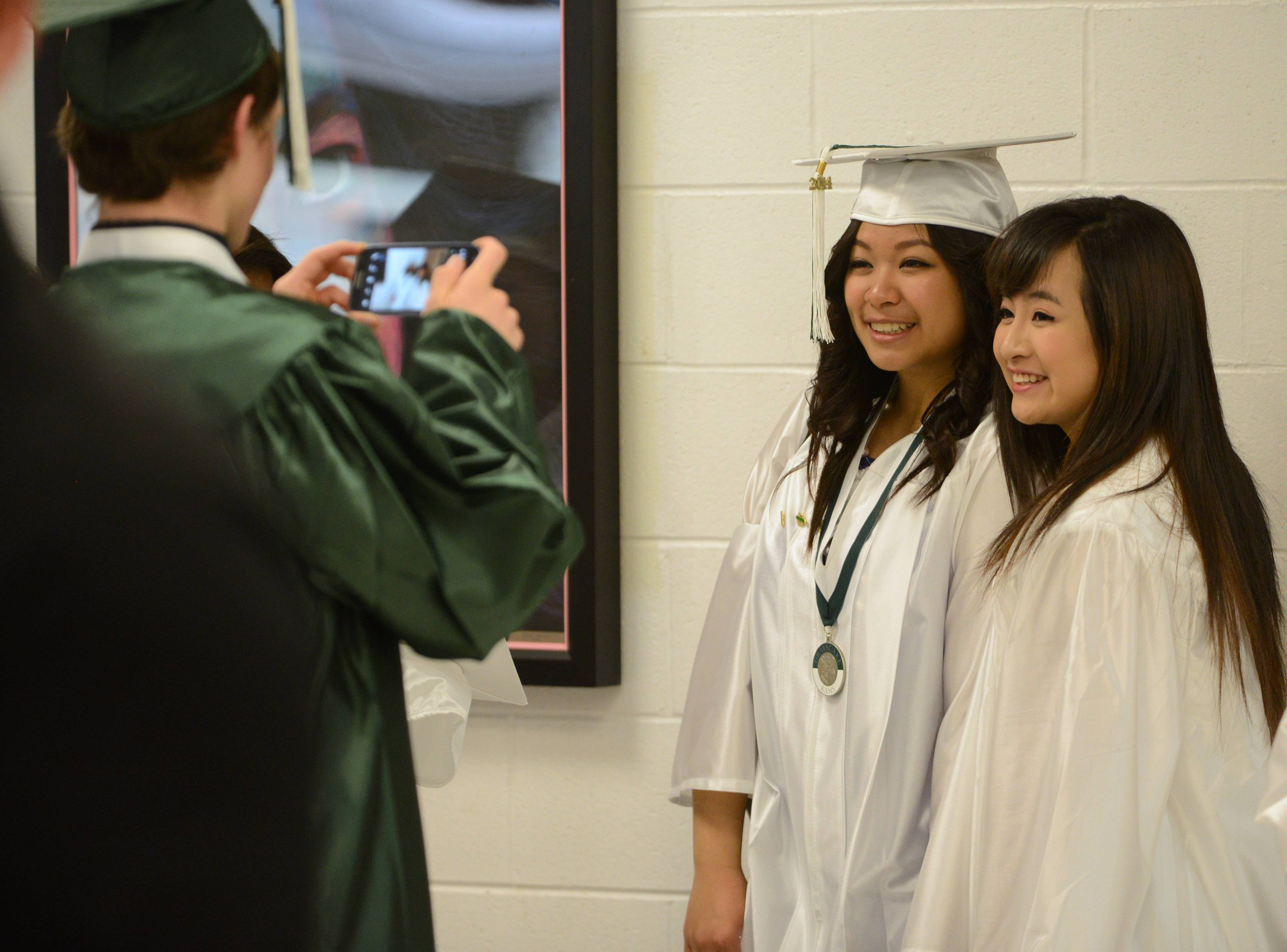 Grayslake Central's Evan Riley, left, takes a photo of Leanne Jamora, center, and Giahan Phan Sunday at the school's graduation ceremony.