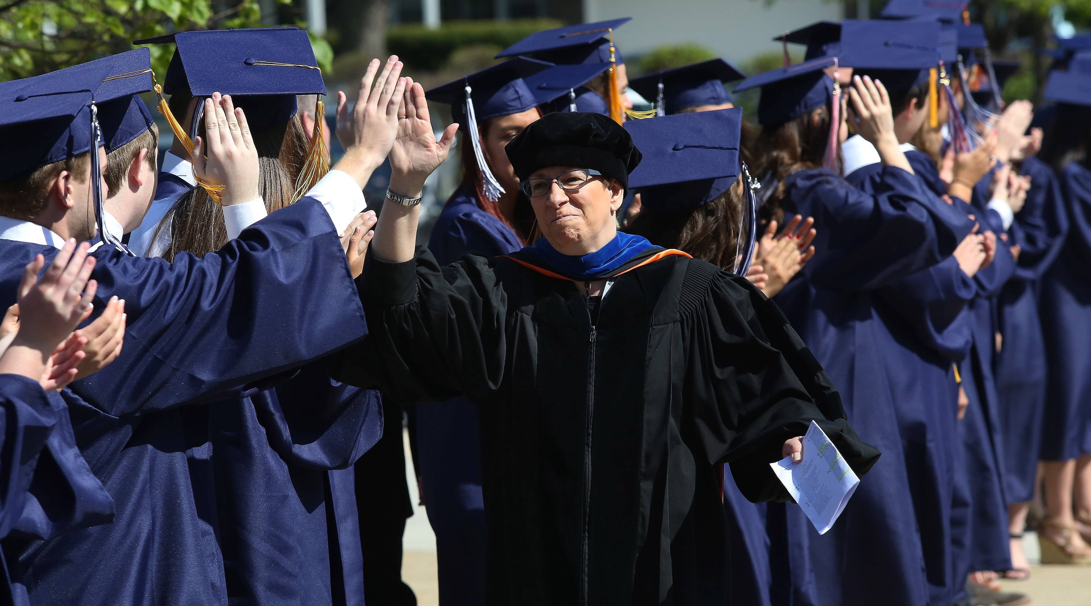 Faculty member Dr. Deborah Scerbicke is congratulated by students during the procession of the 51st Annual Commencement Sunday at St. Viator High School In Arlington Heights. There were 250 graduating seniors receiving their diplomas this year.