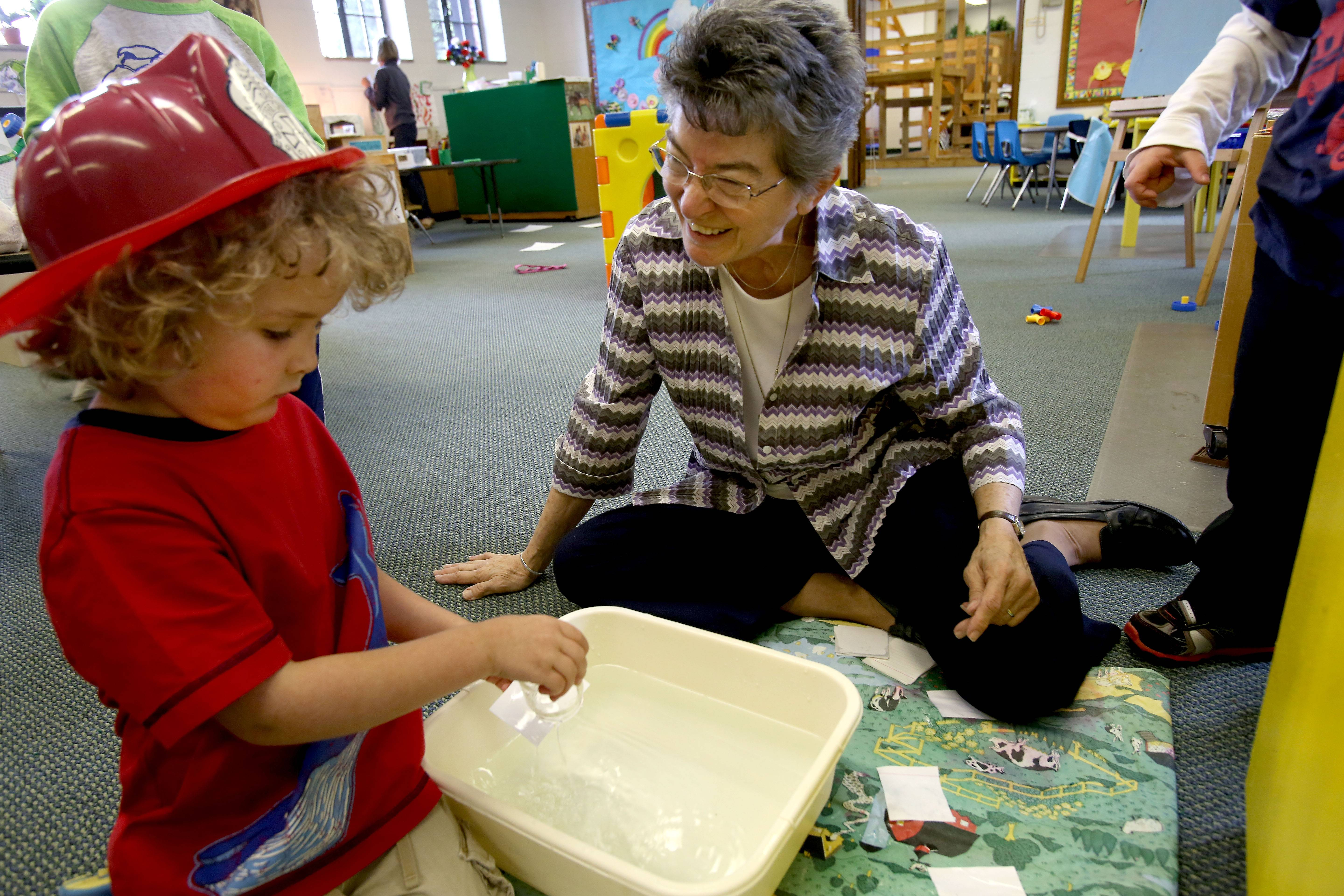 Sister Julie Stapleton helps Jacob Wilson, 4, with a science experiment at the Loretto Early Childhood Center in Wheaton.