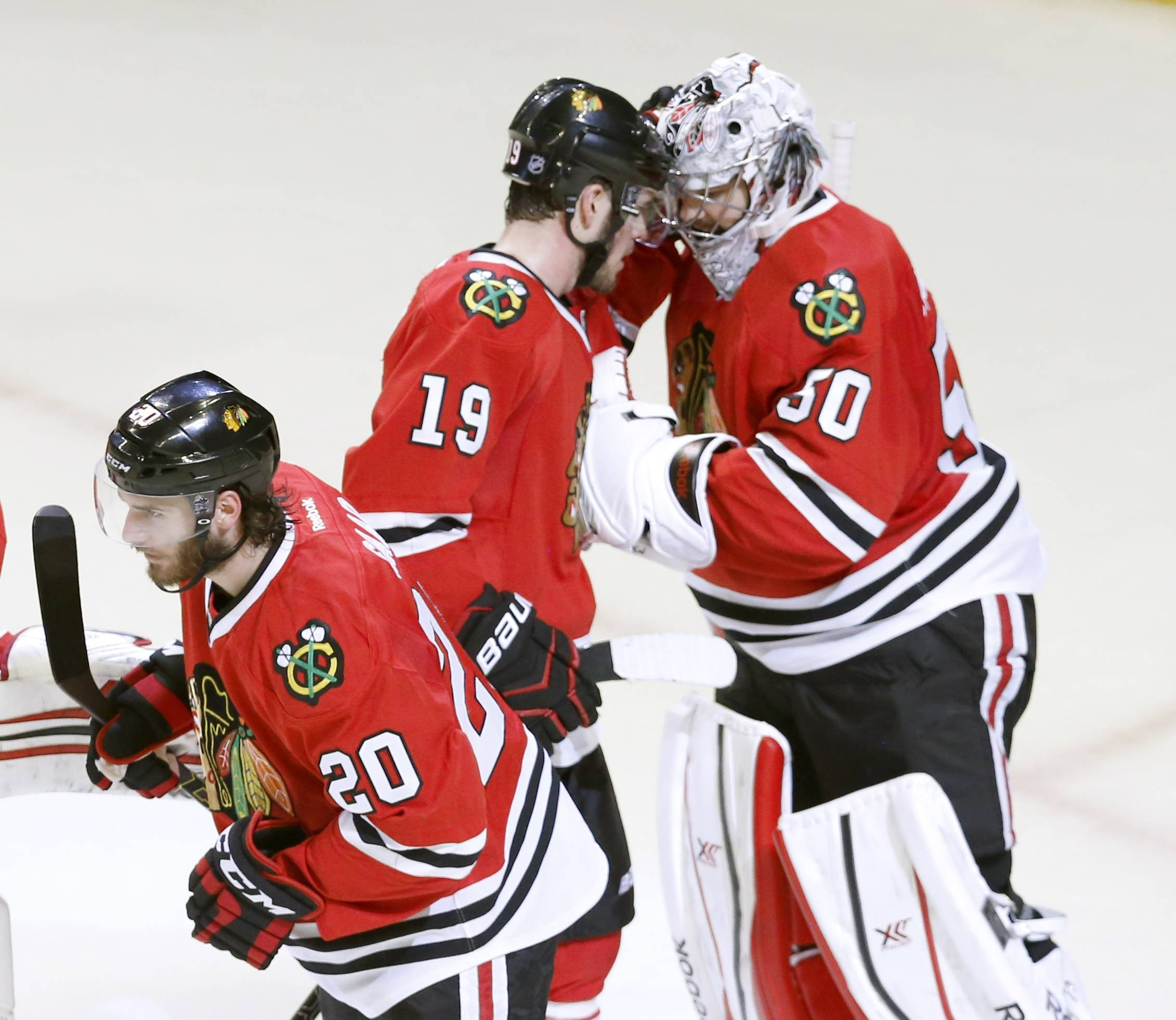 Chicago Blackhawks goalie Corey Crawford, right, celebrates the Blackhawks' 3-1 win over the Los Angeles Kings with Jonathan Toews (19) and Brandon Saad (20) after Game 1 of the Western Conference finals in the NHL hockey Stanley Cup playoffs in Chicago on Sunday, May 18, 2014. The Blackhawks won 3-1.