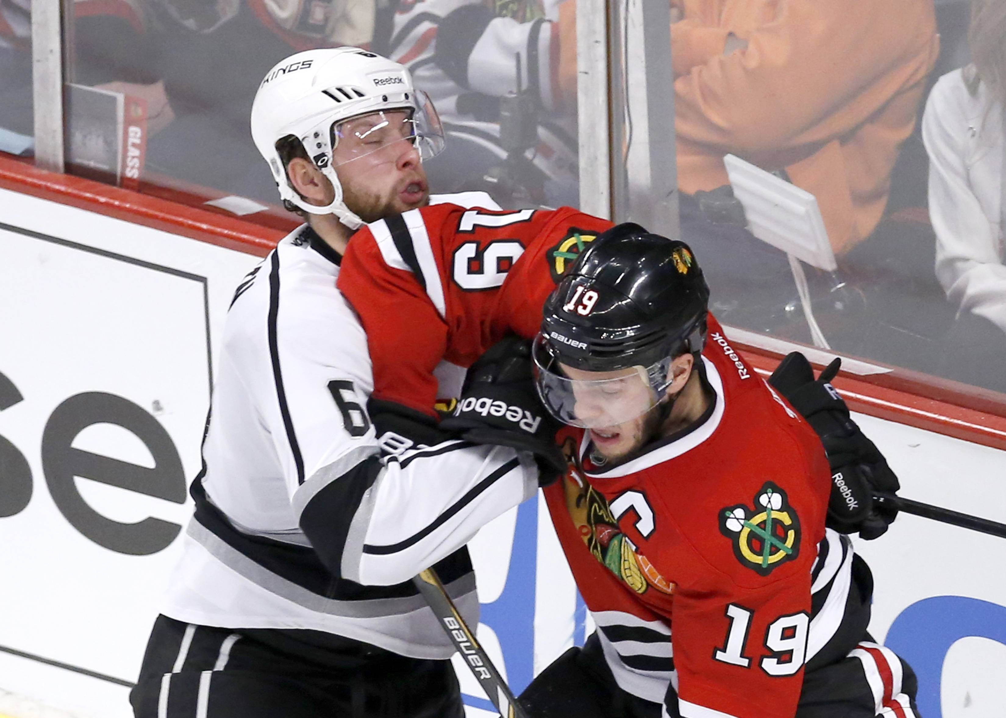 Chicago Blackhawks center Jonathan Toews (19) battles Los Angeles Kings defenseman Jake Muzzin during the second period of Game 1 of the Western Conference finals in the NHL hockey Stanley Cup playoffs in Chicago on Sunday, May 18, 2014.