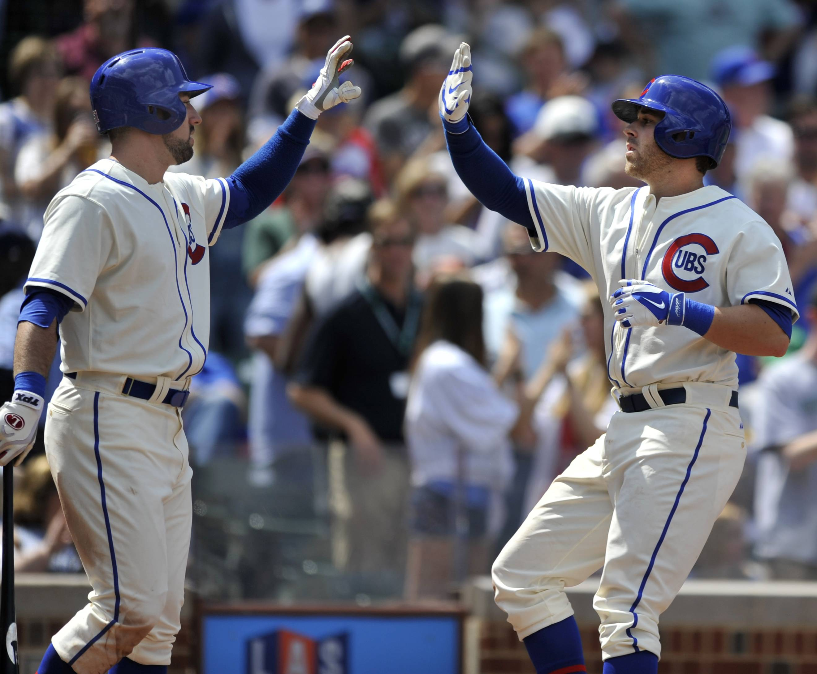 The Cubs' MIke Olt, right, celebrates with teammate Ryan Kalish after hitting a solo home run against the Brewers in the fourth inning Sunday at Wrigley Field.