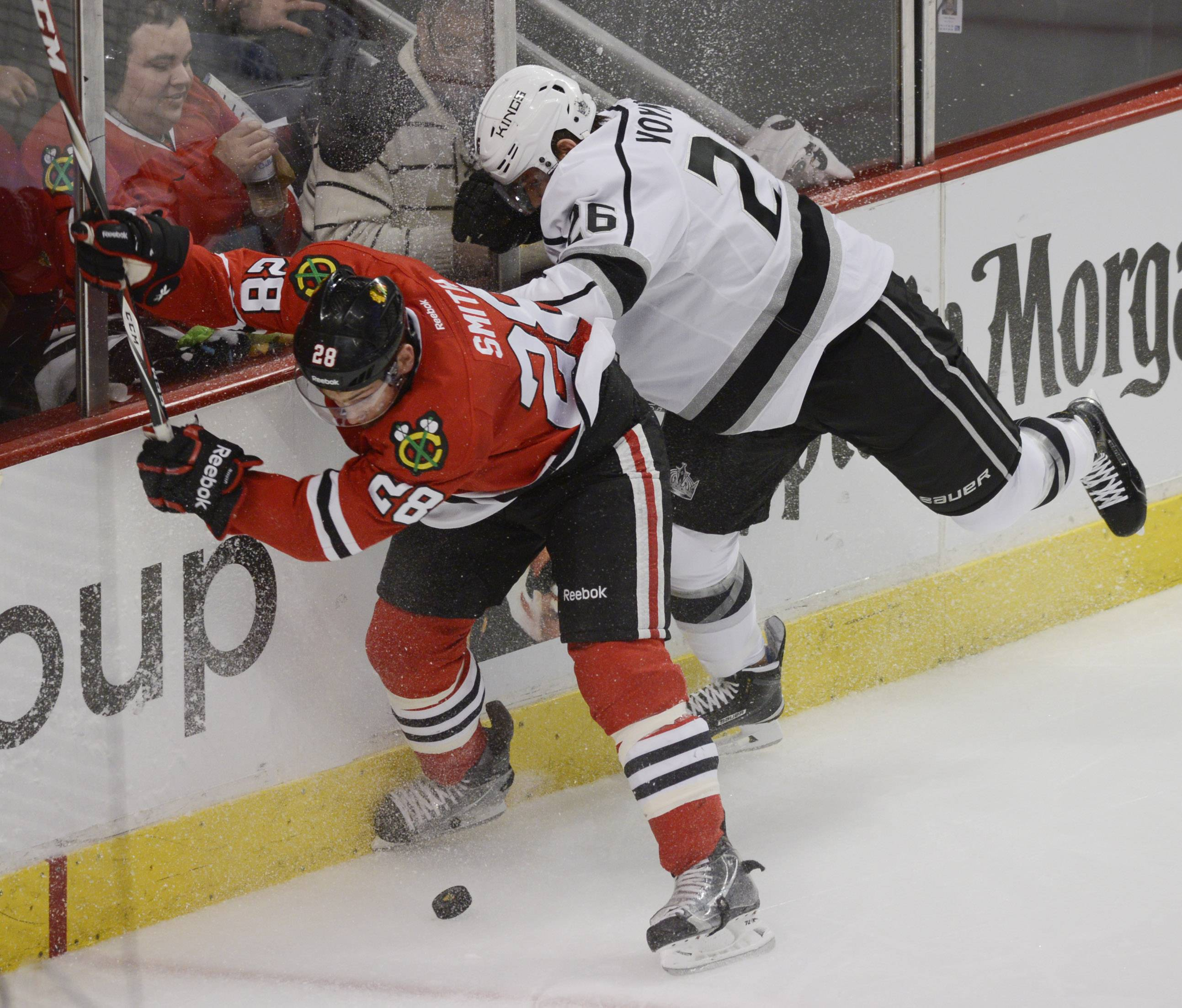 Chicago Blackhawks right wing Ben Smith, left, gets hit by Los Angeles Kings defenseman Slava Voynov the third period of Sunday's game at the United Center in Chicago.