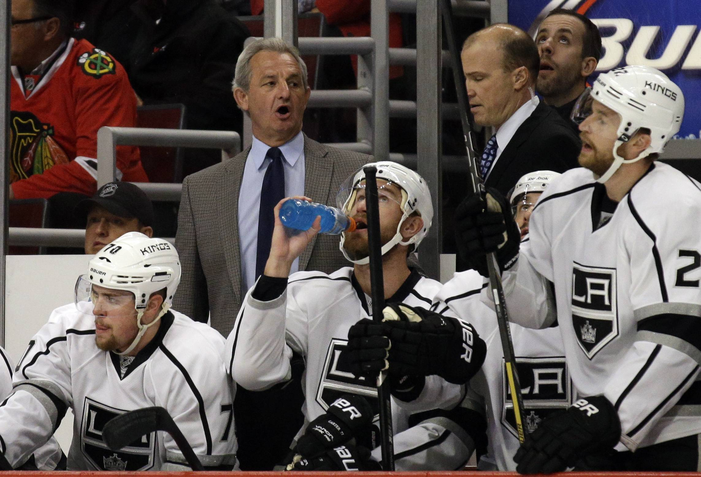 Los Angeles Kings head coach Darryl Sutter, top left, talks to his team during the first period.